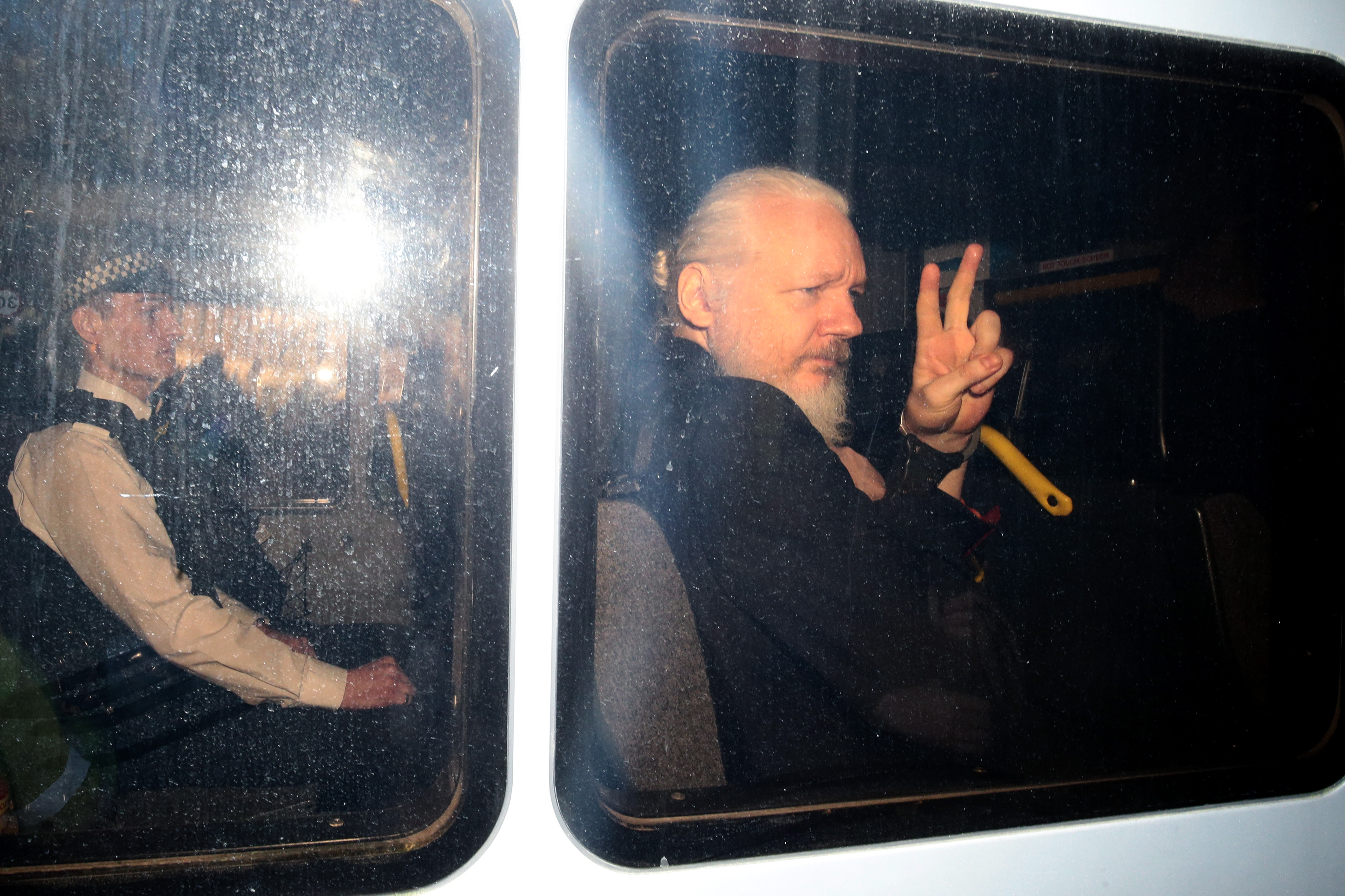 Julian Assange gestures to the media from a police vehicle on his arrival at Westminster Magistrates court on April 11, 2019 in London, England. (Photo by Jack Taylor/Getty Images)