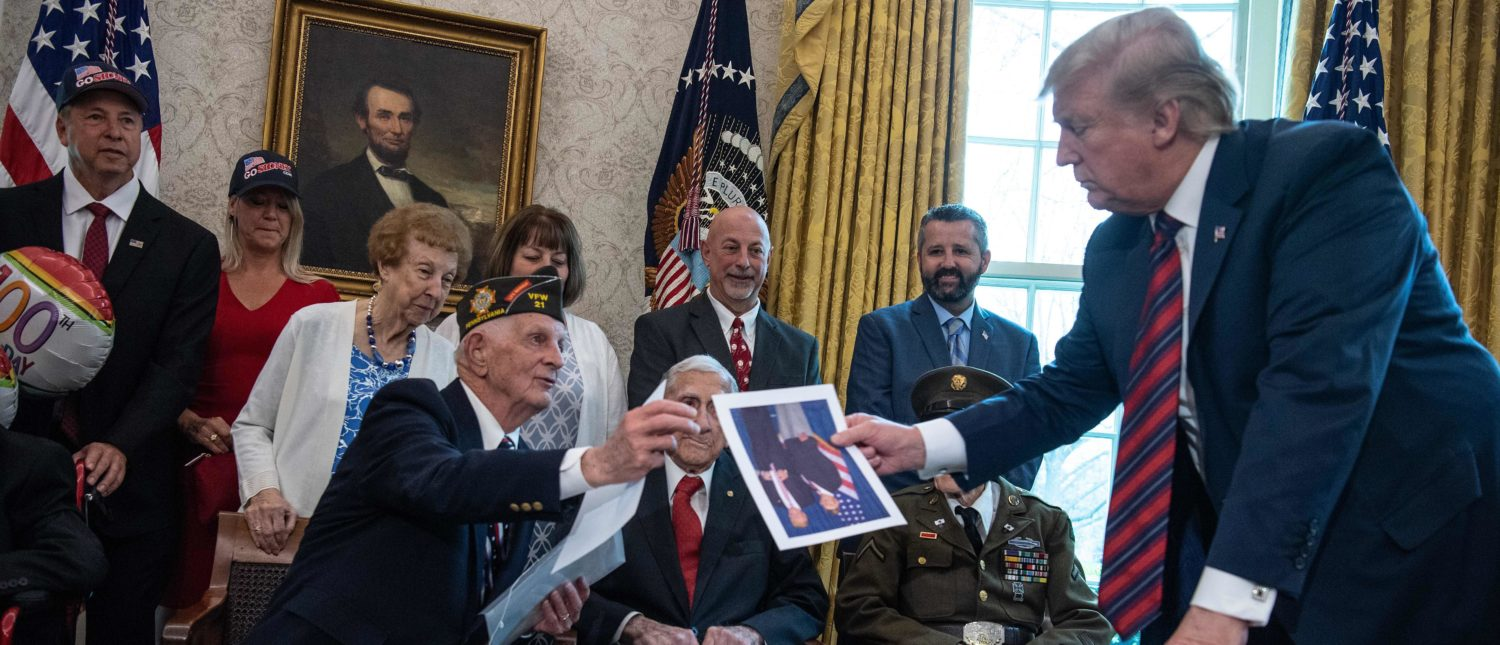 WWII veteran Allen Jones hands US President Donald Trump a picture of the two of them to be signed as Trump meets with WWII veterans and their families in the Oval Office at the White House in Washington, DC, on April 11, 2019. (Photo by NICHOLAS KAMM / AFP) (Photo credit should read NICHOLAS KAMM/AFP/Getty Images)