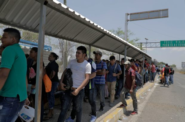 "Honduran migrants wait at the international border bridge in Ciudad Tecun Uman, Guatemala, as they wait to cross into Mexico on April 12, 2019. - A group of 350 Central American migrants forced their way into Mexico Friday, authorities said, as a new caravan of around 2,500 people arrived -- news sure to draw the attention of US President Donald Trump. Mexico's National Migration Institute said some members of the caravan had a ""hostile attitude"" and had attacked local police in the southern town of Metapa de Dominguez after crossing the border from Guatemala. (Photo by Rodrigo Mendez / AFP) (Photo credit should read RODRIGO MENDEZ/AFP/Getty Images)"