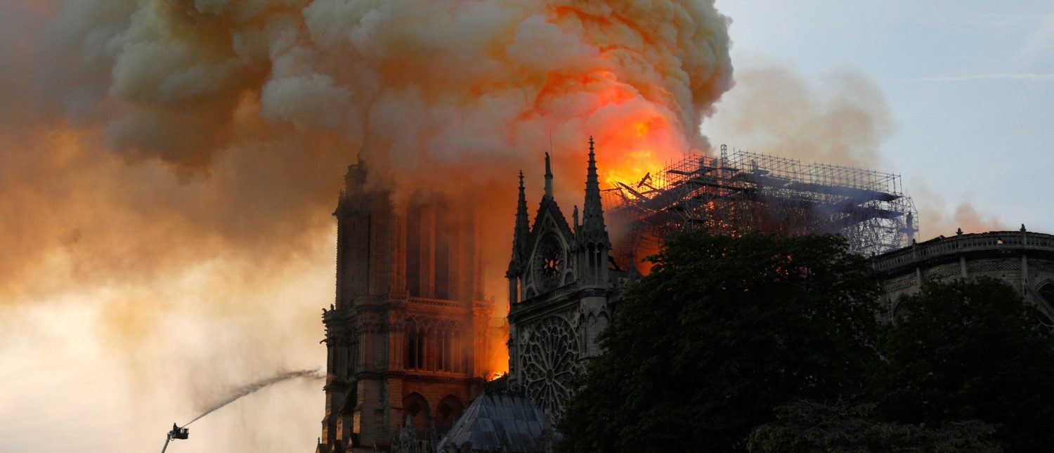 TOPSHOT - A firefighter uses a hose to douse flames and smoke billowing from the roof at Notre-Dame Cathedral in Paris on April 15, 2019. (Photo: GEOFFROY VAN DER HASSELT/AFP/Getty Images)