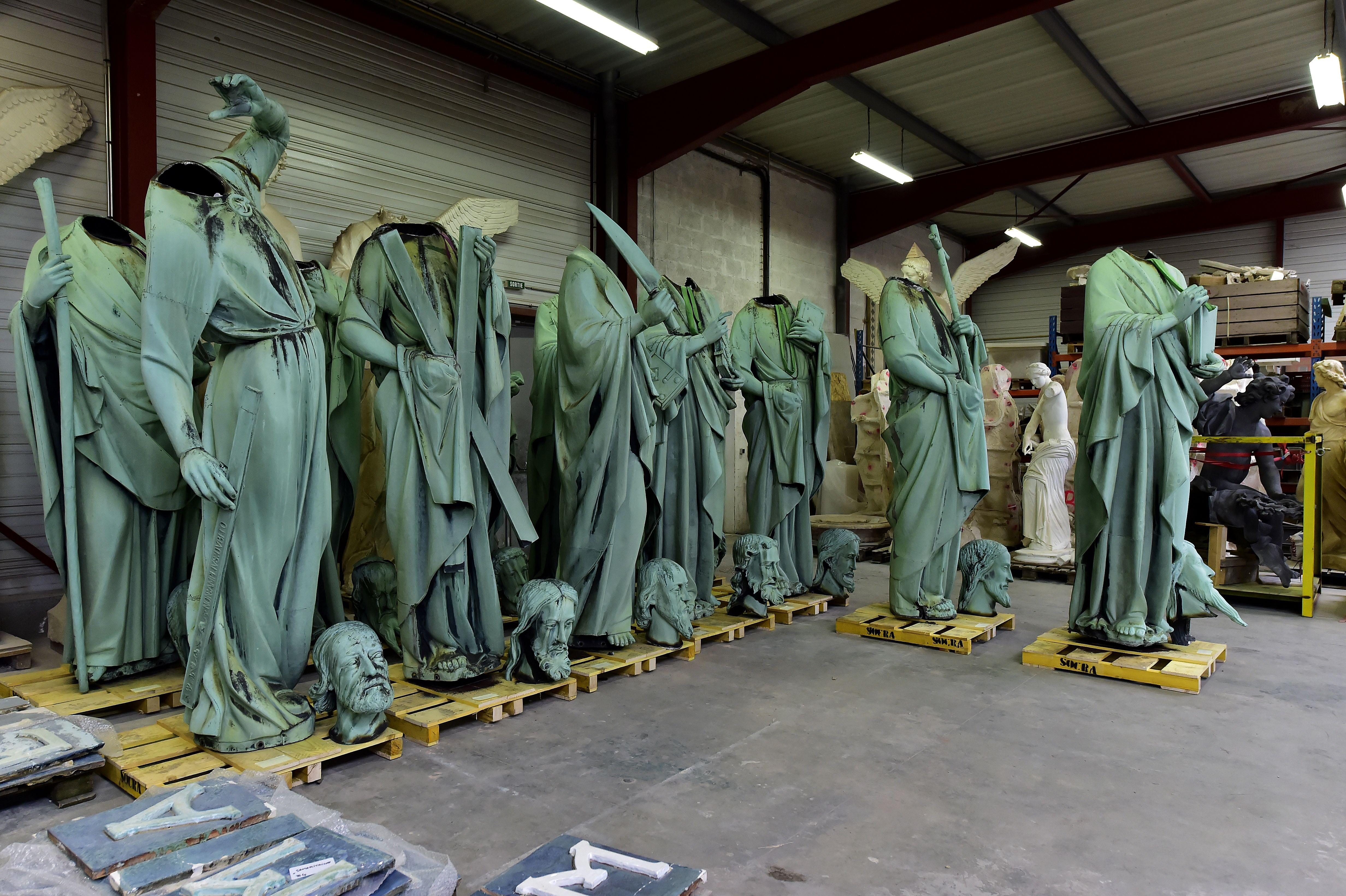 A picture taken in Marsac-sur-Isle near Bordeaux, on April 16, 2019 shows statues which sat around the spire of the Notre-Dame cathedral in Paris, stored in SOCRA workshop before restoration. (Photo: GEORGES GOBET/AFP/Getty Images)