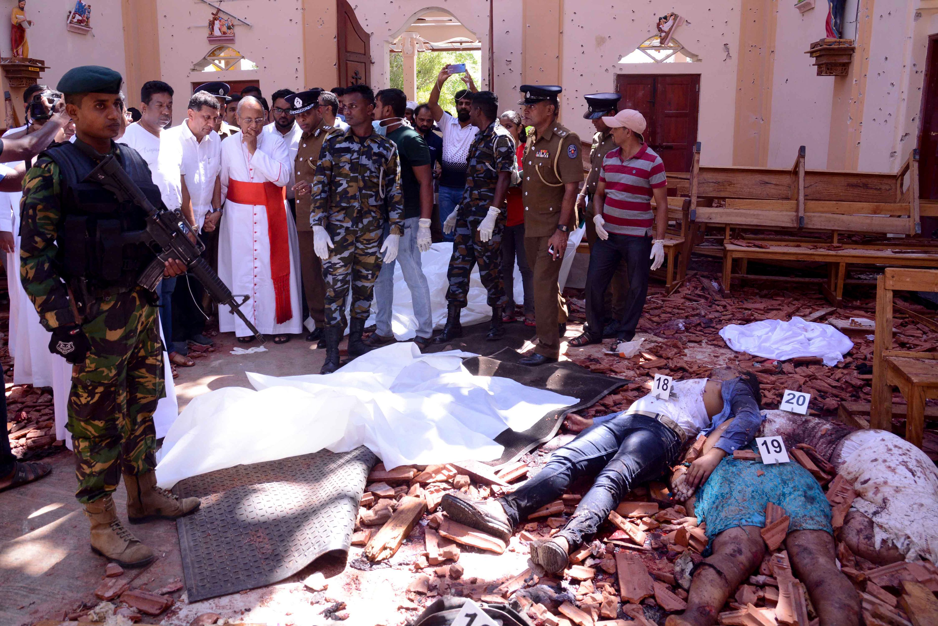 Sri Lanka soldiers and religious members of the parish look on inside the St Sebastian's Church at Katuwapitiya in Negombo on April 21, 2019, following a bomb blast during the Easter service that killed tens of people. (STR/AFP/Getty Images)