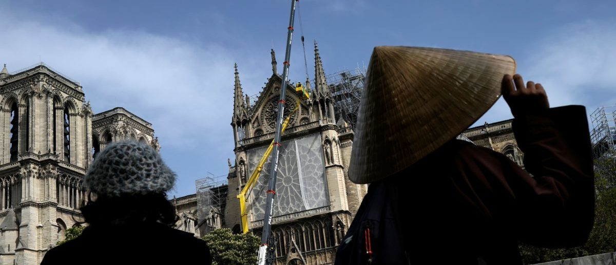 TOPSHOT - Bystanders look on as workers cover and protect the Rosette of Notre-Dame de Paris Cathedral in Paris on April 22, 2019, seven days after a fire devastated the cathedral. LIONEL BONAVENTURE/AFP/Getty Images