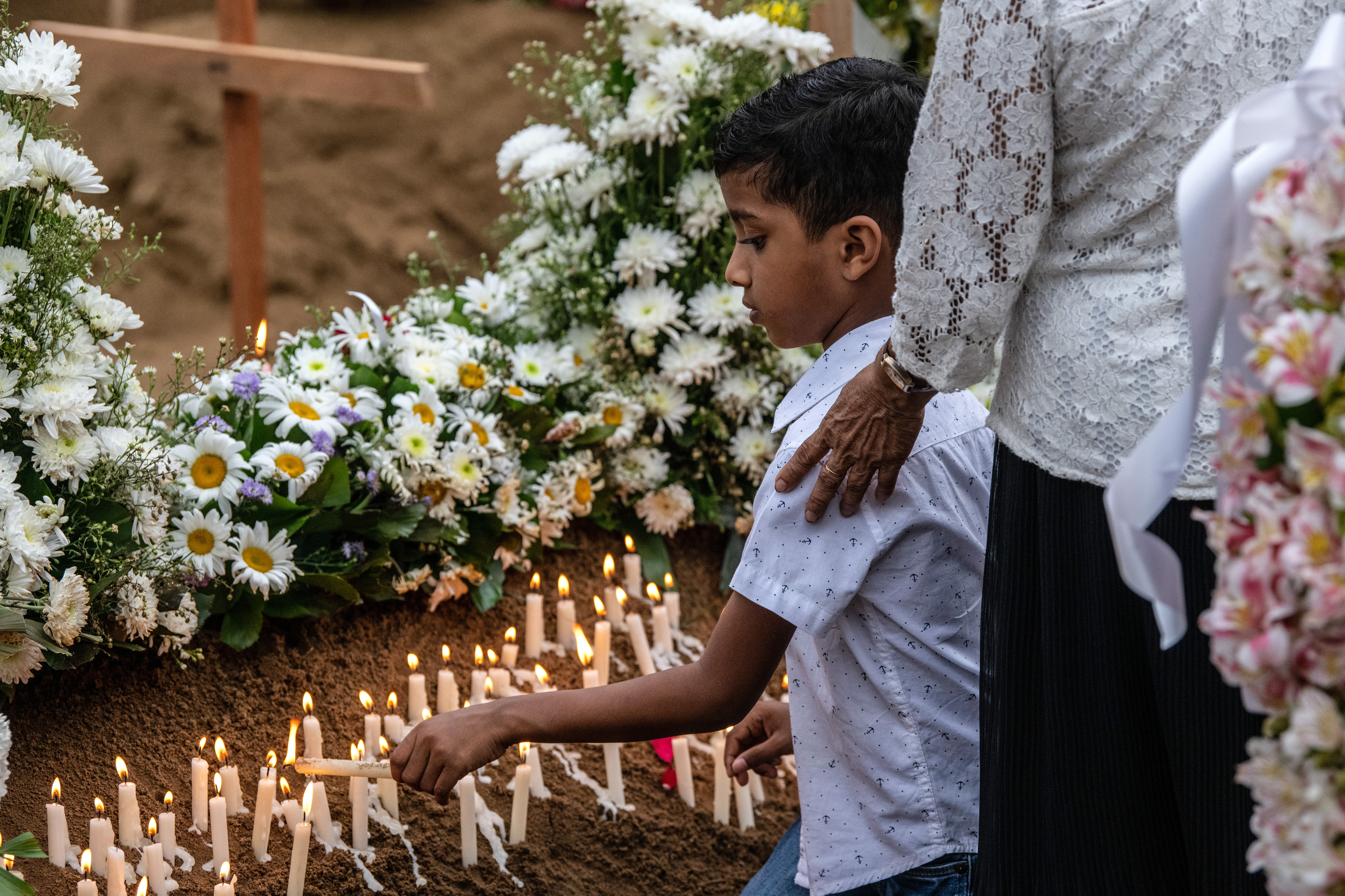 A young boy lights a candle at a grave after a funeral for a person killed in the Easter Sunday attack on St Sebastian's Church, on April 25, 2019 in Negombo, Sri Lanka.(Photo by Carl Court/Getty Images)