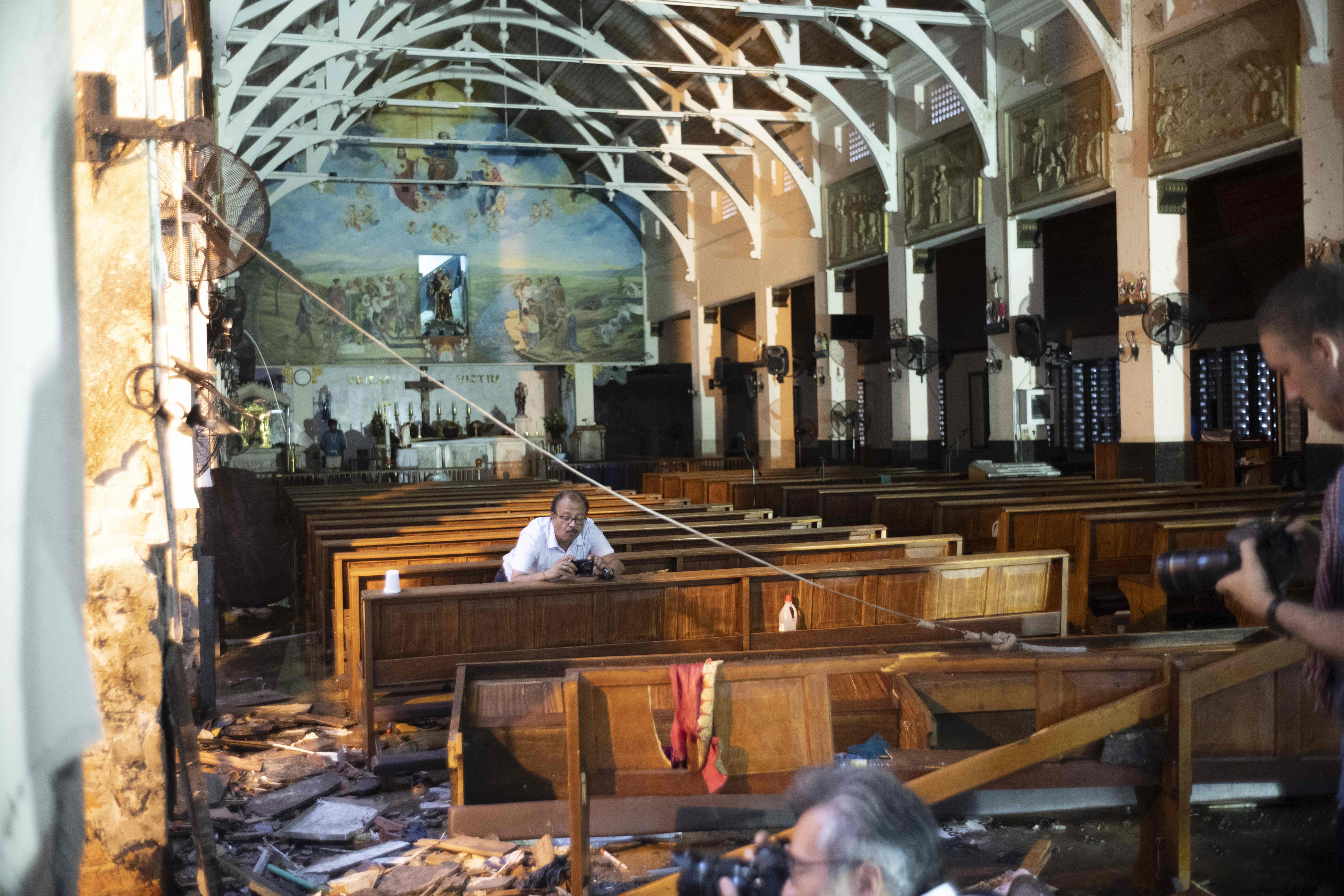 Journalists take pictures inside St. Anthony's Shrine in Colombo on April 26, 2019, following a series of bomb blasts targeting churches and luxury hotels on Easter Sunday in Sri Lanka. (JEWEL SAMAD/AFP/Getty Images)