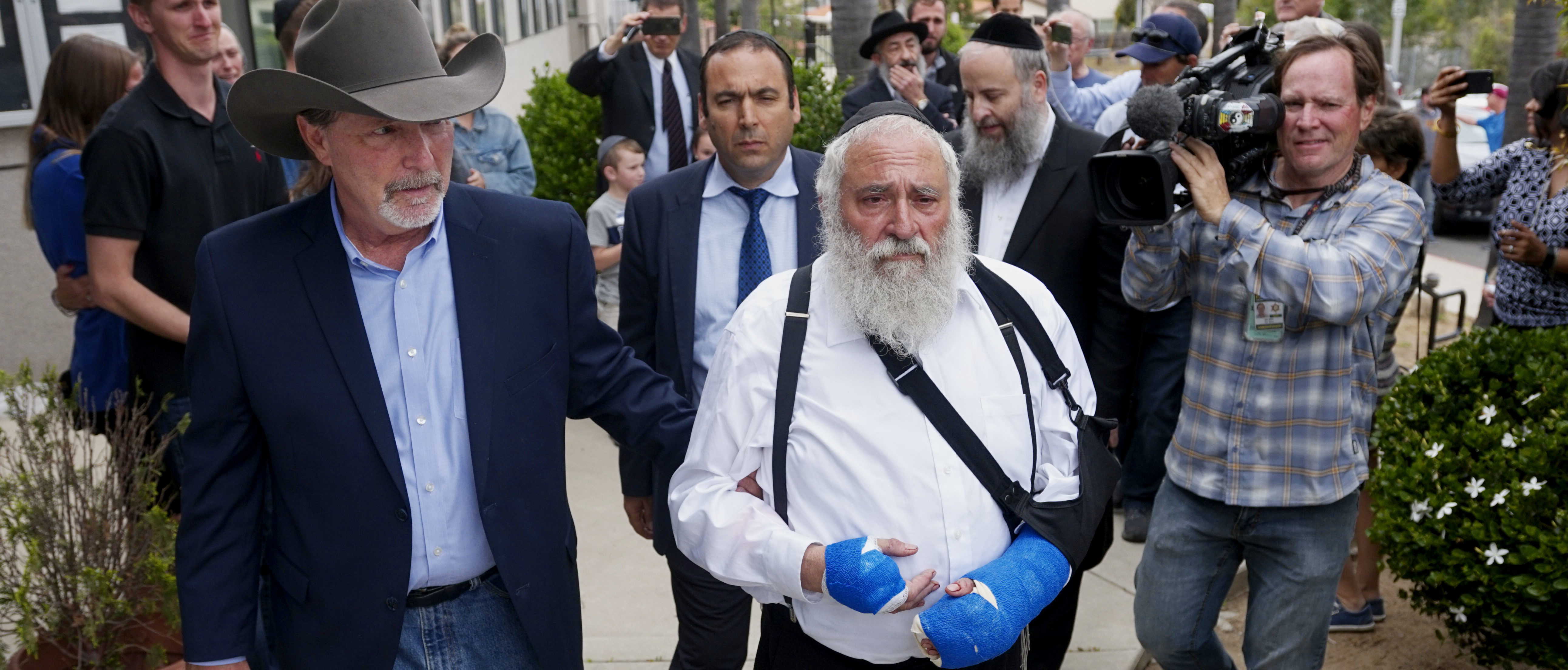 "Executive Director Rabbi Yisroel Goldstein, who was shot in the hands, walks towards a press conference with Poway Mayor Steve Vaus outside of the Chabad of Poway Synagogue on April 28, 2019 in Poway, California. - A rabbi who carried on preaching despite being wounded in the latest deadly shooting at a US synagogue said on April 28 that Jews would not be intimidated by the ""senseless hate"" of anti-semitism. (Photo by SANDY HUFFAKER / AFP) (Photo credit should read SANDY HUFFAKER/AFP/Getty Images)"