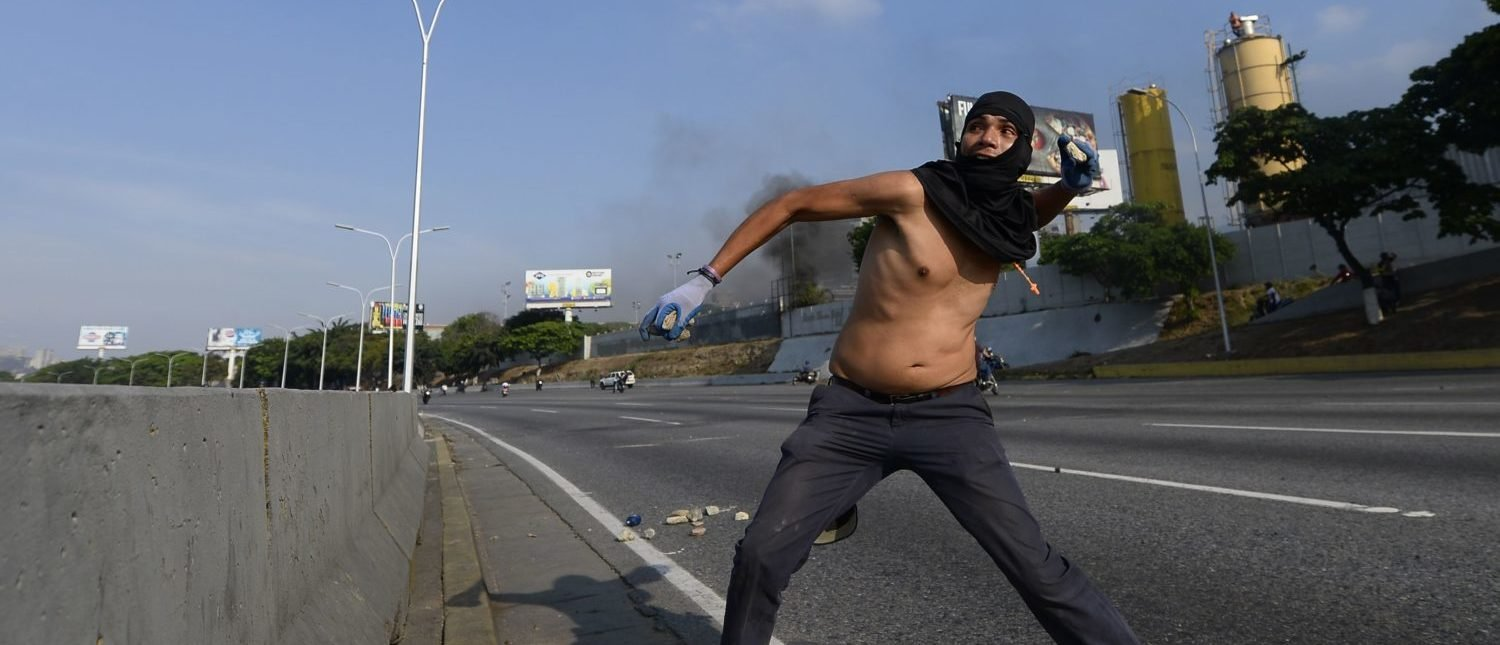 A Venezuelan clashes with security forces in Caracas on April 30, 2019. - Venezuelan opposition leader and self-proclaimed acting president Juan Guaido said on Tuesday that troops had joined his campaign to oust President Nicolas Maduro as the government vowed to put down what it said was an attempted coup. (Photo by MATIAS DELACROIX/AFP/Getty Images)