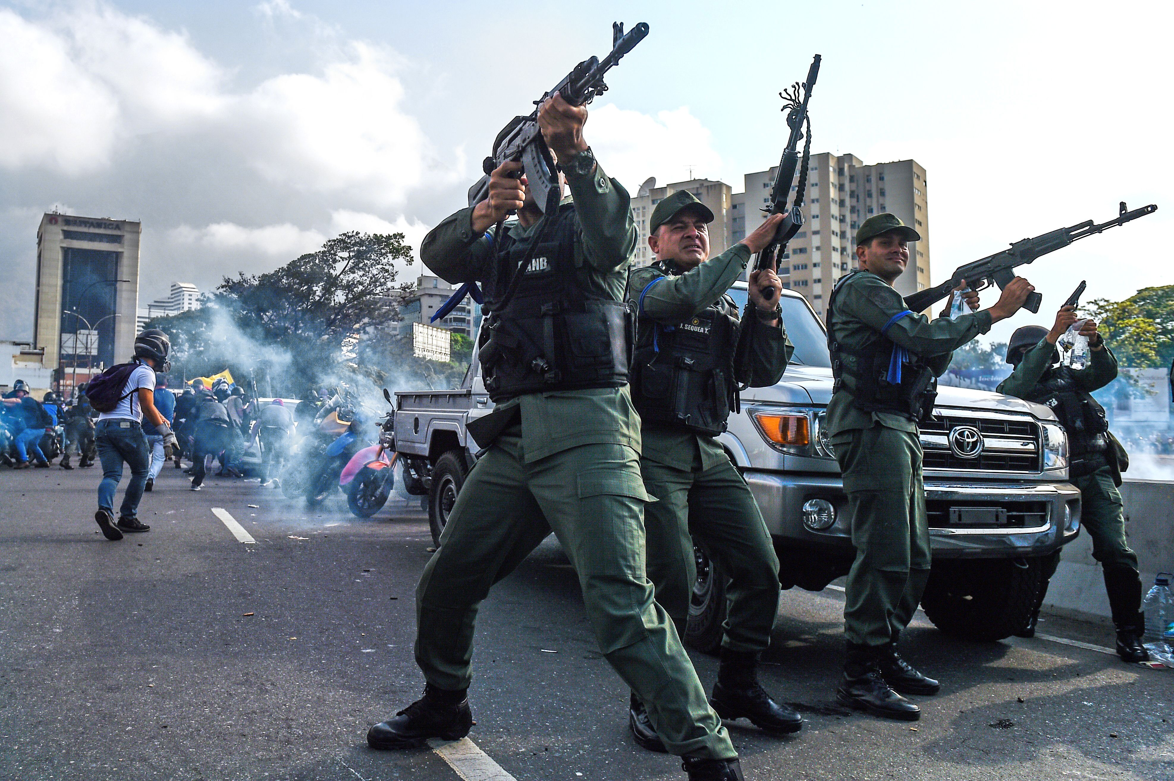 "Members of the Bolivarian National Guard who joined Venezuelan opposition leader and self-proclaimed acting president Juan Guaido fire into the air to repel forces loyal to President Nicolas Maduro who arrived to disperse a demonstration near La Carlota military base in Caracas on April 30, 2019. - Guaido -- accused by the government of attempting a coup Tuesday -- said there was ""no turning back"" in his attempt to oust President Nicolas Maduro from power. (Photo by FEDERICO PARRA/AFP/Getty Images)"