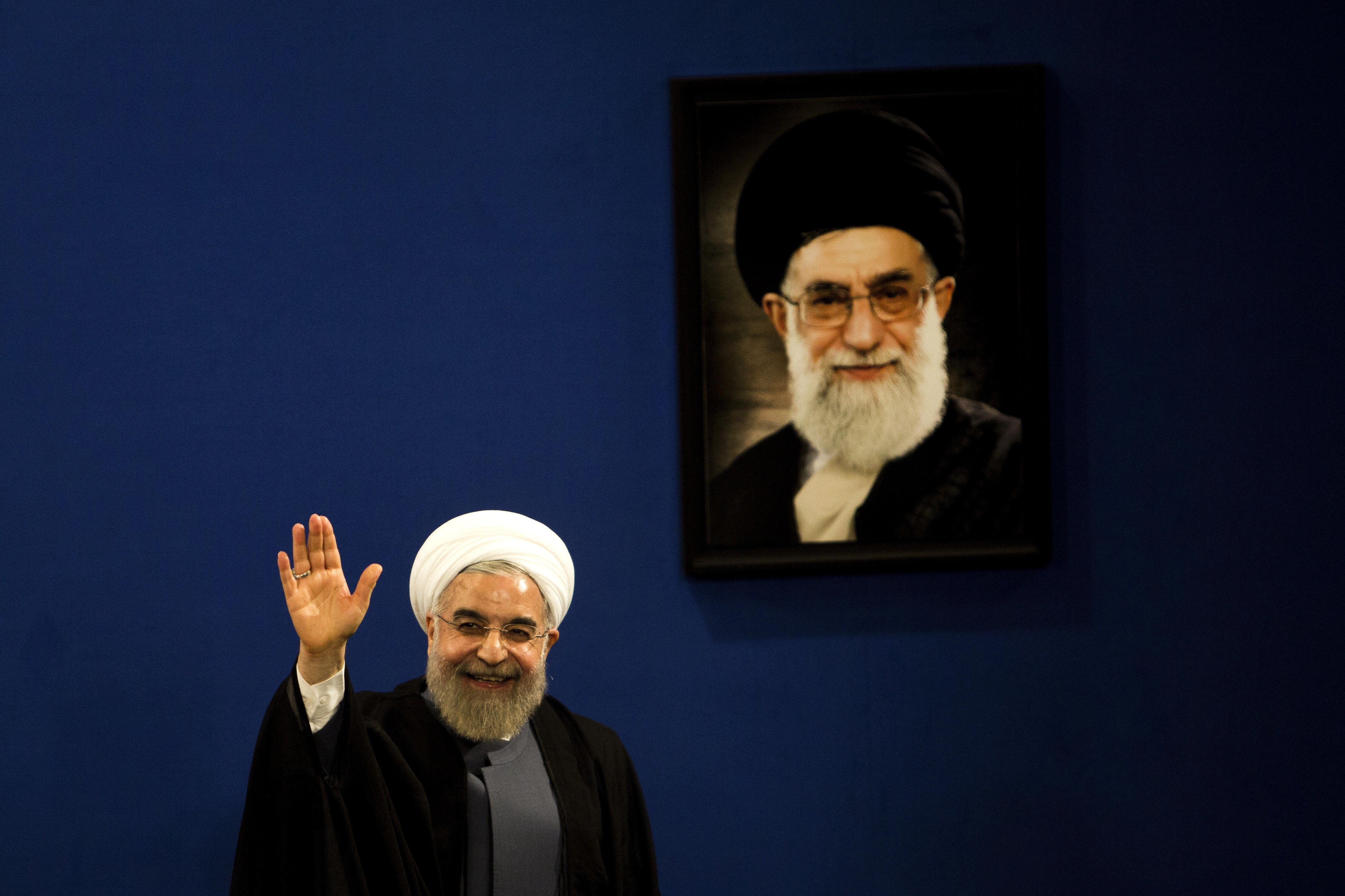 Iranian President Hassan Rouhani waves to journalists next to a portrait of supreme leader Ayatollah Ali Khamenei (R) at the end of a press conference in Tehran on June 13, 2015. (BEHROUZ MEHRI/AFP/Getty Images)