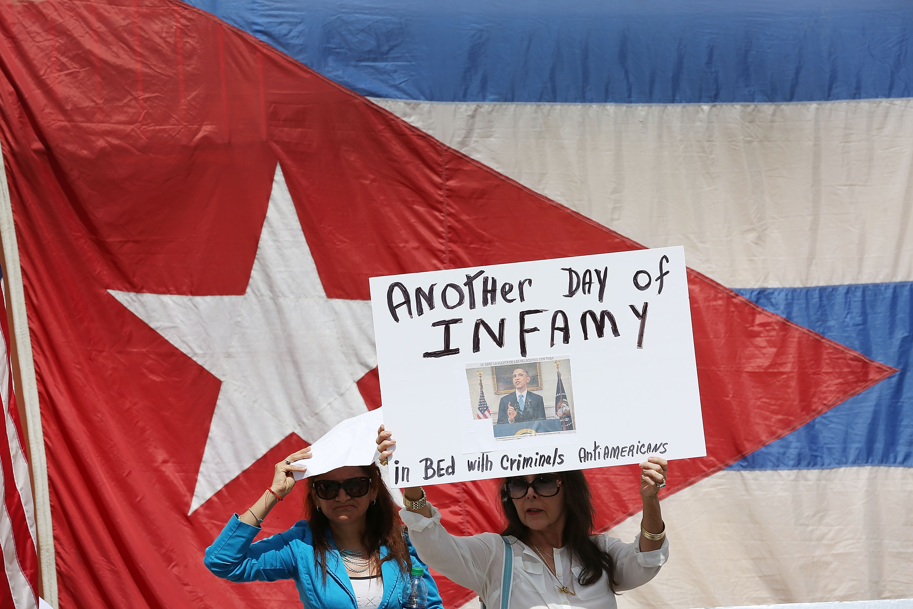 Laura Via Nelly holds a sign that reads, 'Another Day of Infamy', as she shows her displeasure, in the Little Havana neighborhood, with the normalization of the Cuban/United States relationship as the Cuban Embassy opens after a 54 year absence in Washington, DC on July 20, 2015 in Miami, Florida. The United States and Cuba have now established a restoration of full diplomatic relations 54 years after they had ended. (Photo by Joe Raedle/Getty Images)