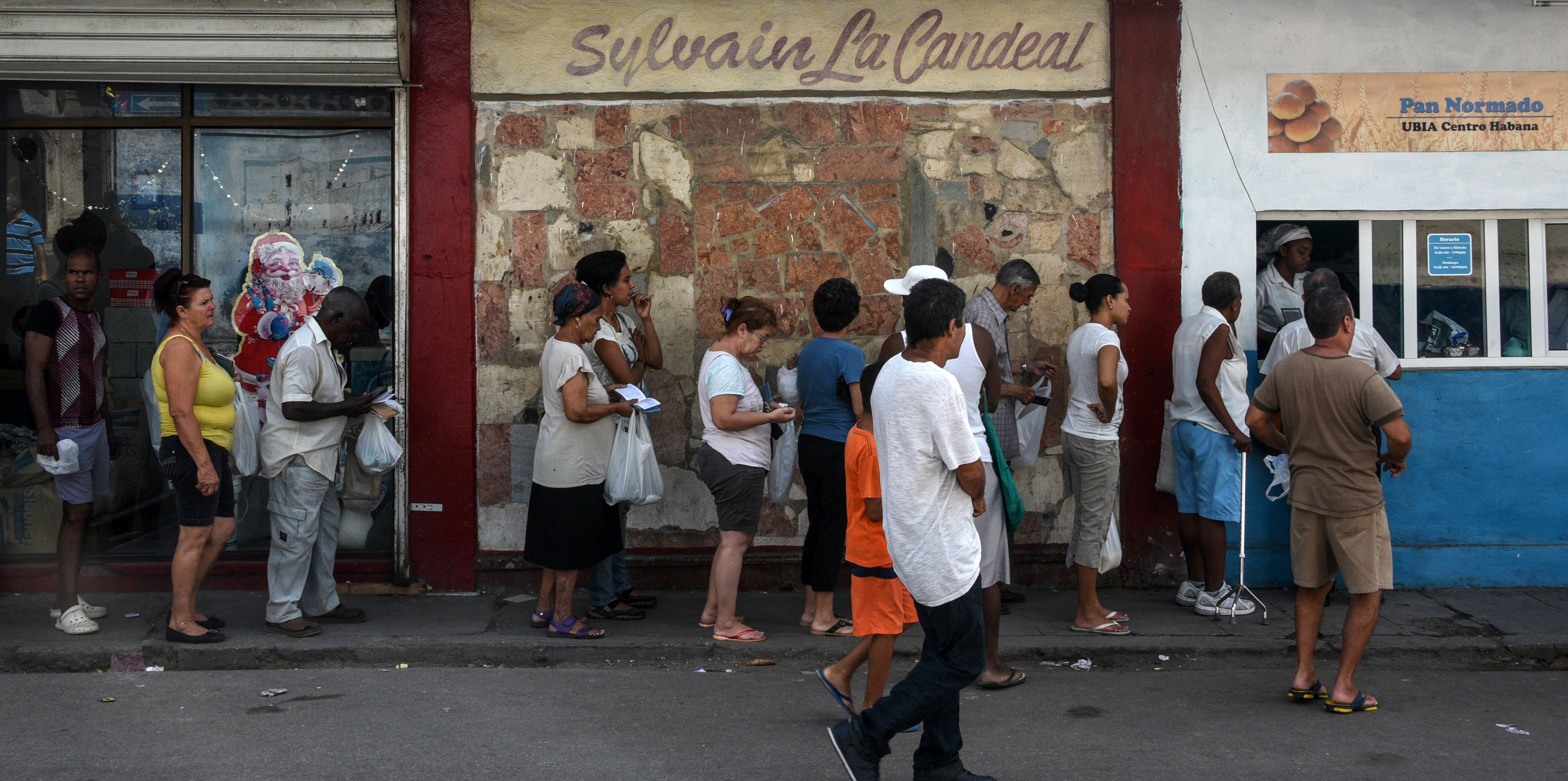 Cubans queue to buy bread in a street of Havana, on March 19, 2016. Political and economic reforms in Cuba will be a no-go area during talks between Cuban leader Raul Castro and US President Barack Obama, Cuban Foreign Minister Bruno Rodriguez said Thursday. Obama will be on Sunday the first sitting US president to visit Cuba since 1928, capping his historic policy of ending a bitter standoff that has endured since Fidel Castro's overthrow of the US-backed government of Fulgencio Batista in 1959. AFP PHOTO/ RODRIGO ARANGUA / AFP / RODRIGO ARANGUA (Photo credit should read RODRIGO ARANGUA/AFP/Getty Images)