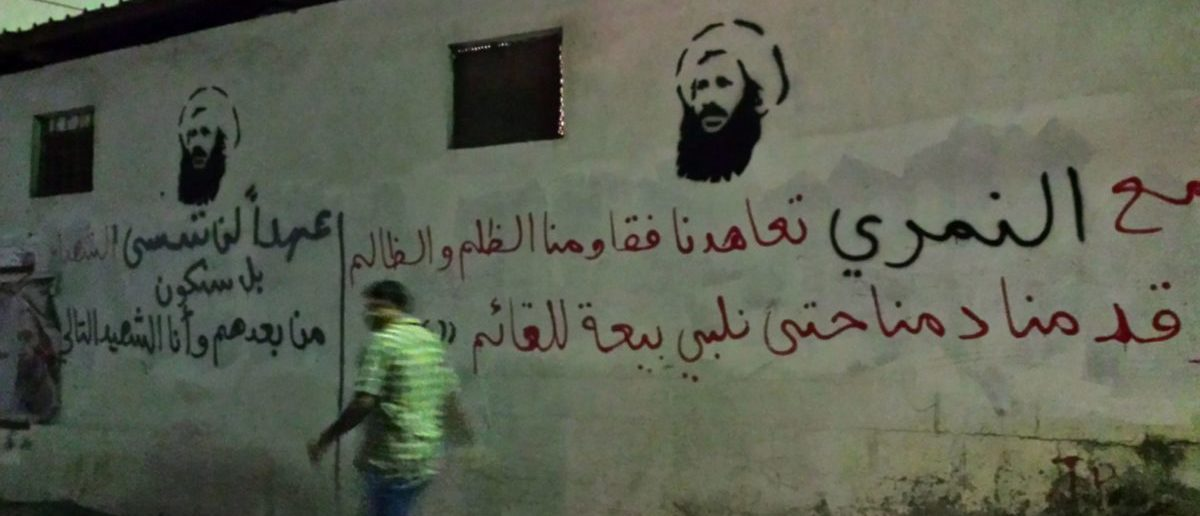 An undated picture taken in 2016 shows a man walking past images of executed Shiite cleric Nimr al-Nimr on a wall in the Awamiya area in Saudi Arabia's Eastern province. (STRINGER/AFP/Getty Images)