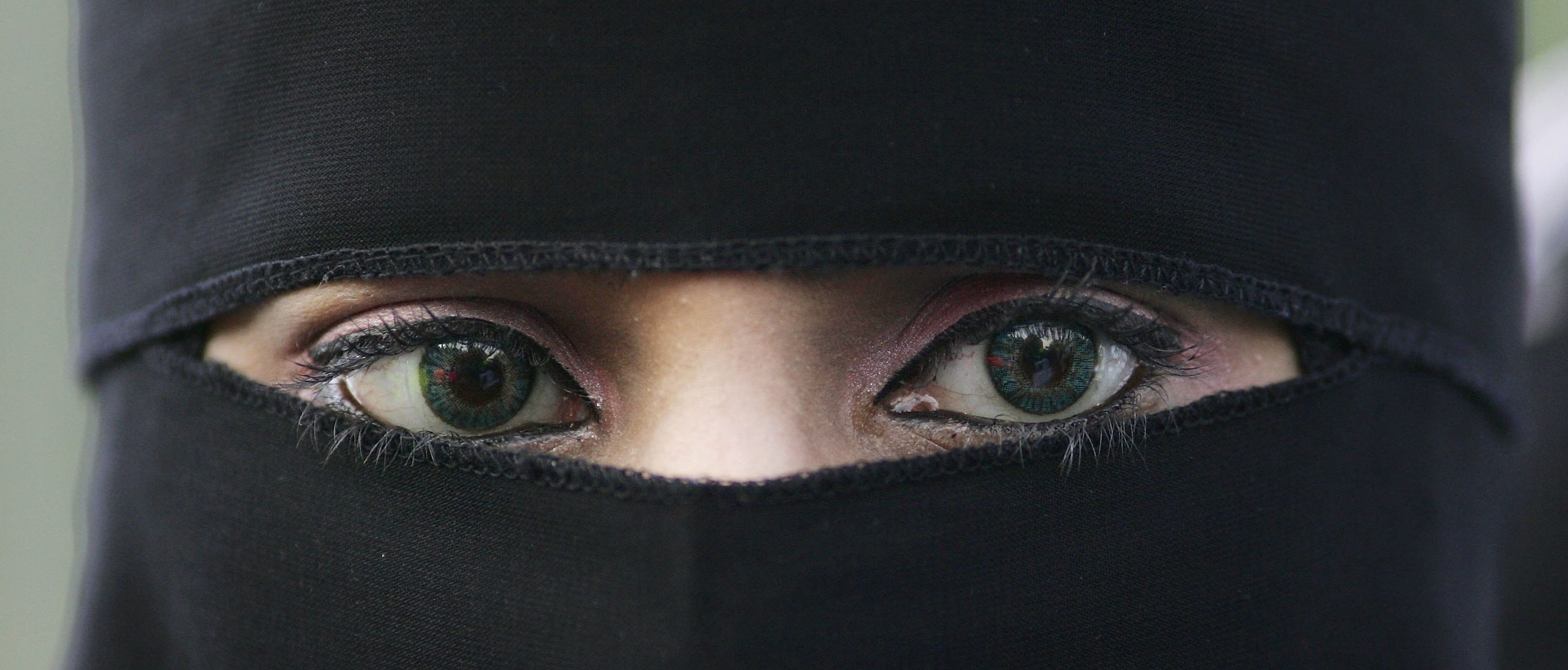 BLACKBURN, UNITED KINGDOM - OCTOBER 14: A Muslim woman wearing a niqab veil protests outside Bangor Street Community centre where Leader of the House of Commons Jack Straw is holding one of his weekend surgery appointments where he faced a protest by around 50 Muslim protesters on October 14, 2006, Blackburn, England. Jack Straw made comments last week regarding his view that veils such as the Burqa and Niqab split communities. (Photo by Christopher Furlong/Getty Images)