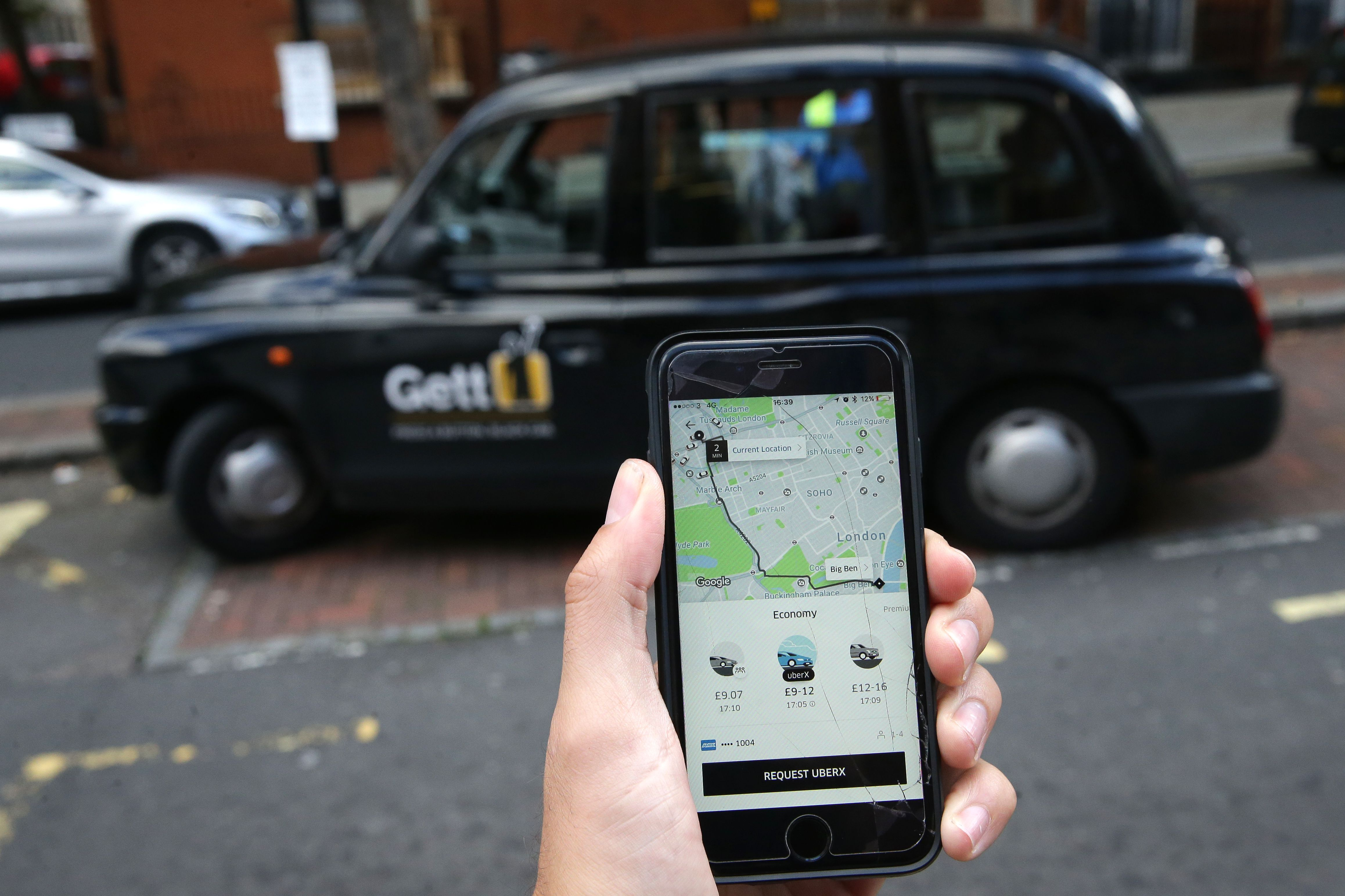A woman poses holding a smartphone showing the App for ride-sharing cab service Uber in London on September 22, 2017. (DANIEL LEAL-OLIVAS/AFP/Getty Images)