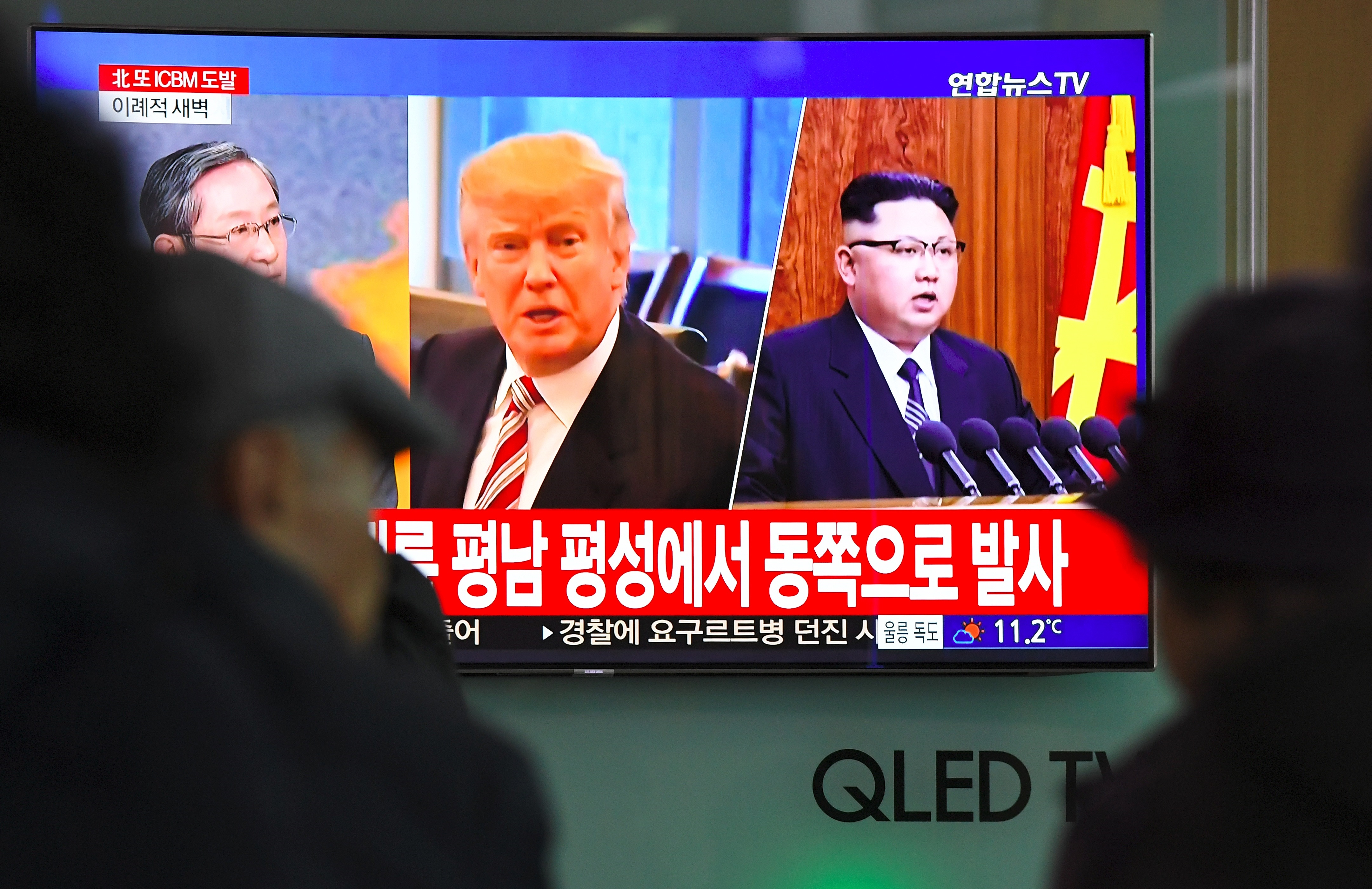 People watch a television news screen showing pictures of US President Donald Trump (C) and North Korean leader Kim Jong-Un (R) at a railway station in Seoul on November 29, 2017. North Korea test fired what appeared to be an intercontinental ballistic missile on November 29, in a major challenge to US President Donald Trump after he slapped fresh sanctions on Pyongyang and declared it a state sponsor of terrorism. JUNG YEON-JE/AFP/Getty Images