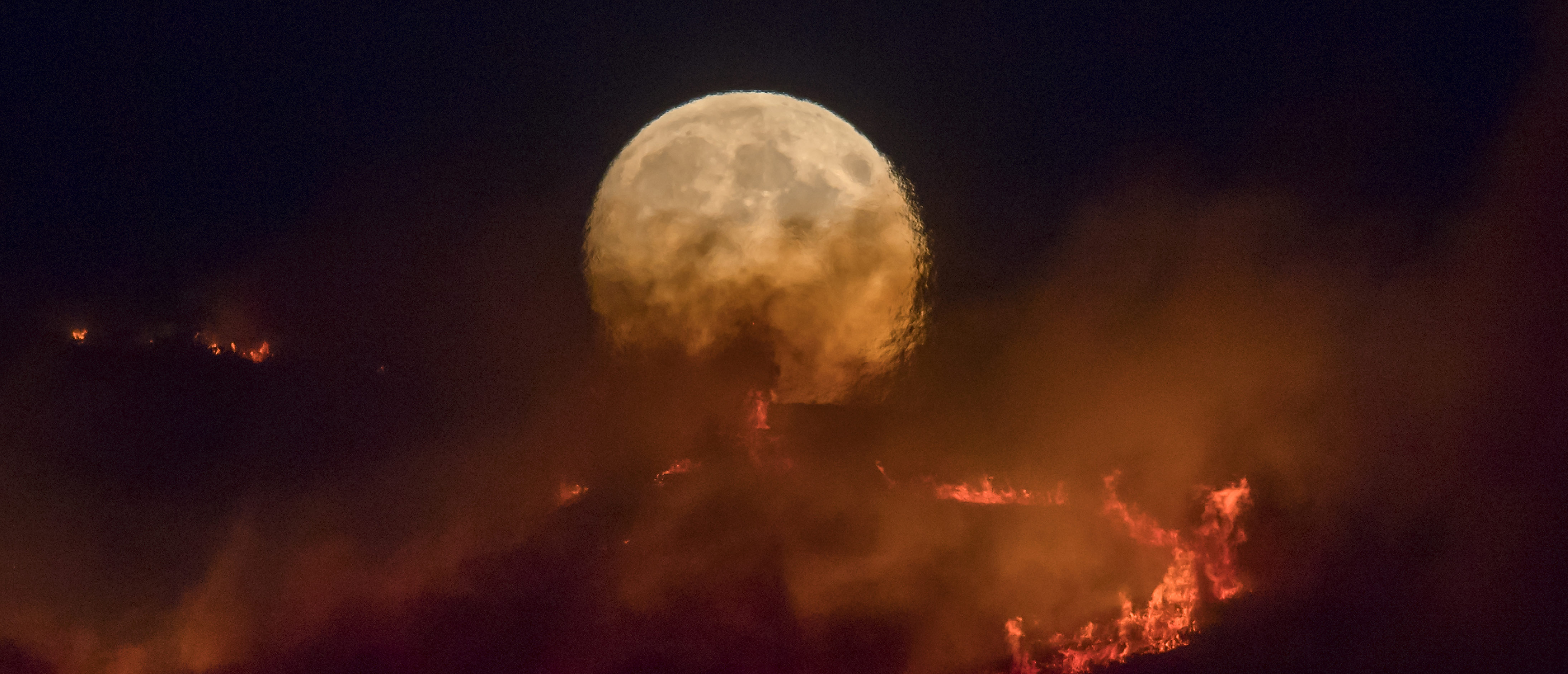 The full moon rises behind burning moorland as a large wildfire sweeps across the moors between Dovestones and Buckton Vale in Stalybridge, Greater Manchester on June 26, 2018 in Stalybridge, England. (Photo by Anthony Devlin/Getty Images)