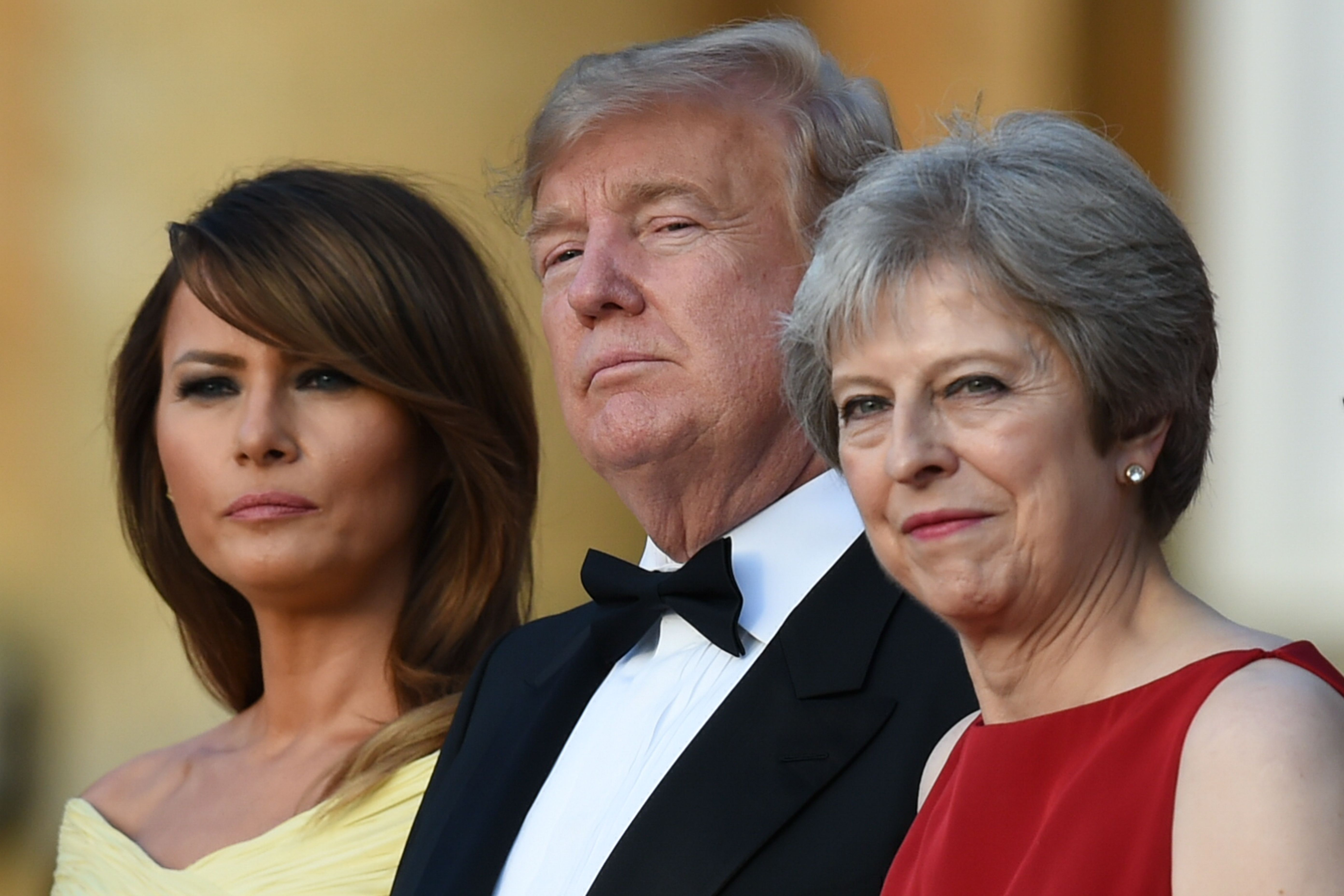 US First Lady Melania Trump, US President Donald Trump and Britain's Prime Minister Theresa May stand on steps in the Great Court as the bands of the Scots, Irish and Welsh Guards perform a ceremonial welcome as they arrive for a black-tie dinner with business leaders at Blenheim Palace, west of London, on July 12, 2018, on the first day of President Trump's visit to the UK. (GEOFF PUGH/AFP/Getty Images)