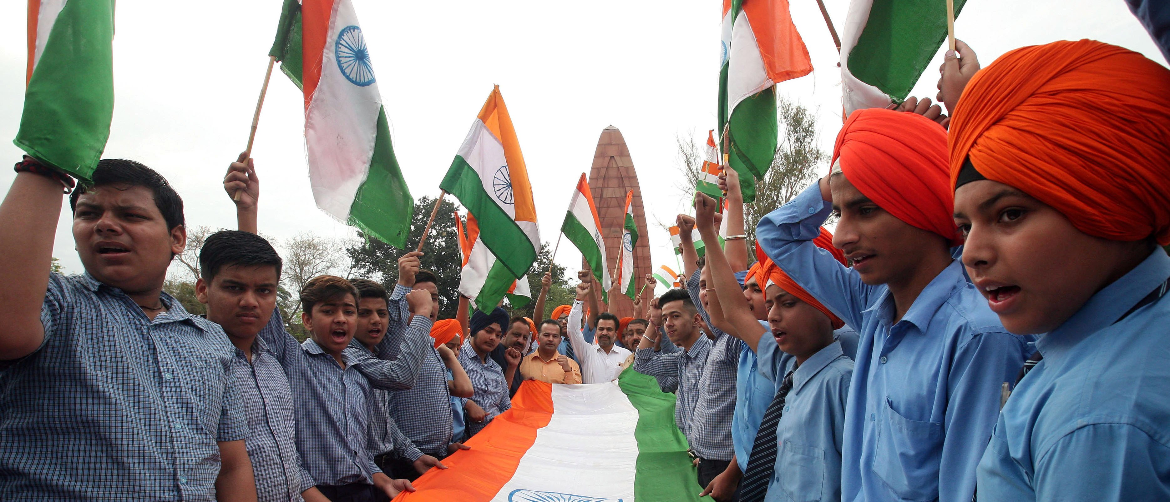 Students hold a giant Indian national flag during a ceremony to pay homage at the Jallianwala Bagh memorial to mark 100th anniversary of Jallianwala Bagh massacre in Amritsar, India, April 12, 2019. REUTERS/Munish Sharma