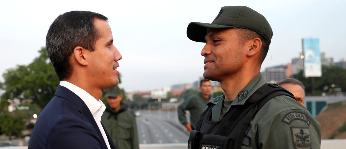 """Venezuelan opposition leader Juan Guaido, who many nations have recognised as the country's rightful interim ruler, shakes hands with a military member near the Generalisimo Francisco de Miranda Airbase """"La Carlota"""", in Caracas, Venezuela April 30, 2019. REUTERS/Carlos Garcia Rawlins"""