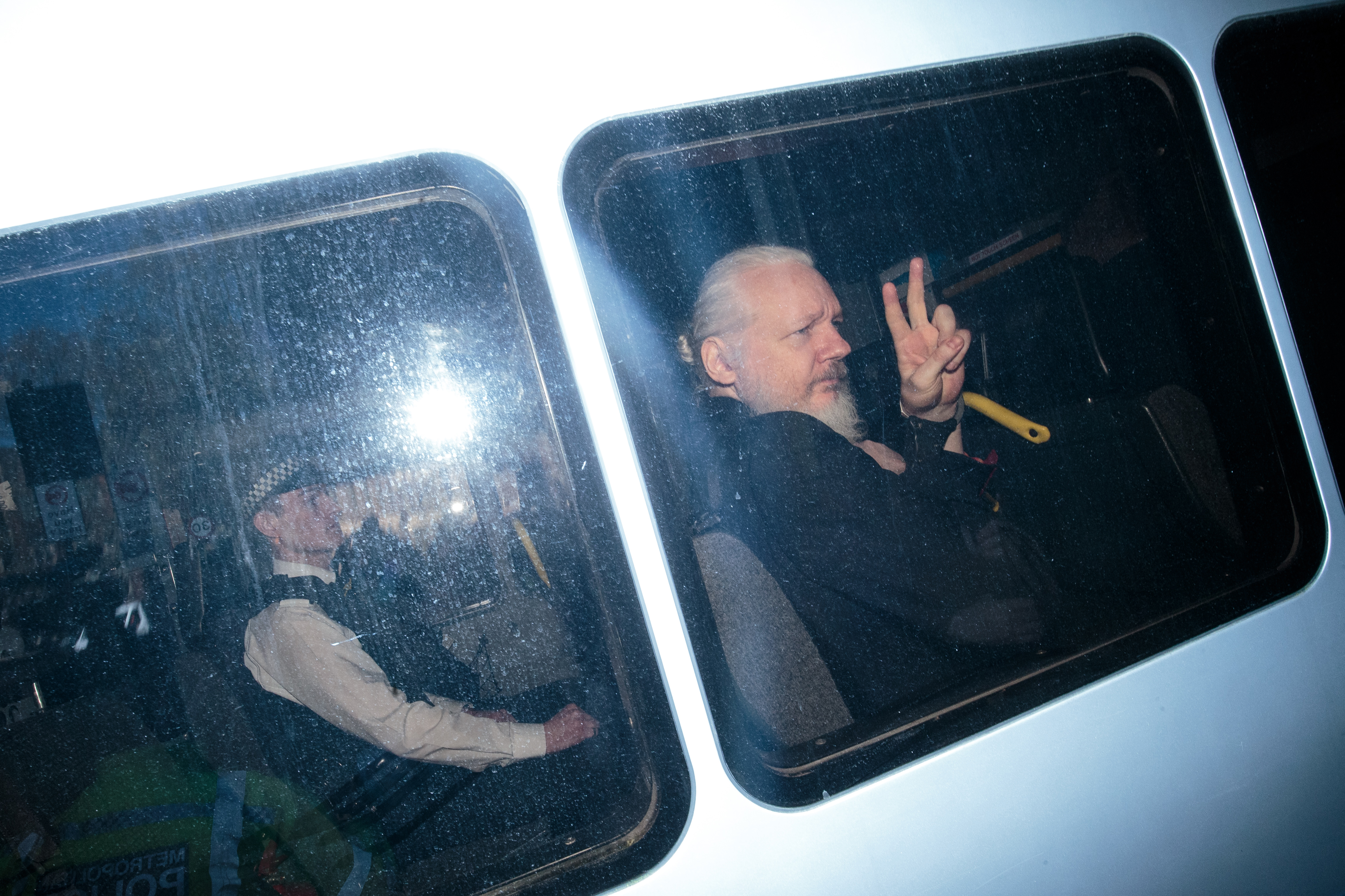 LONDON, ENGLAND - APRIL 11: Julian Assange gestures to the media from a police vehicle on his arrival at Westminster Magistrates court on April 11, 2019 in London, England. (Photo by Jack Taylor/Getty Images)