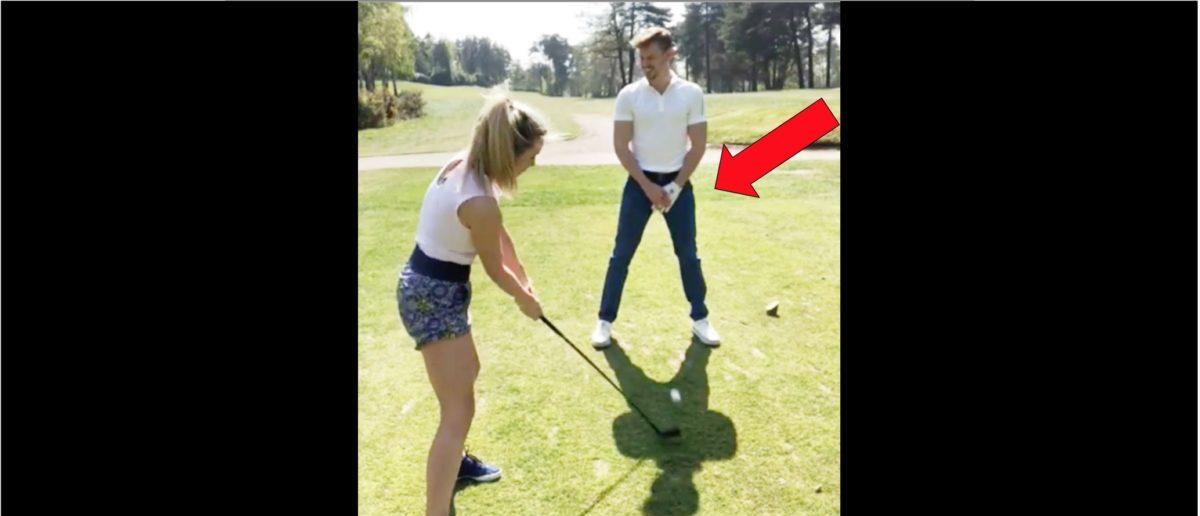 Lucy Robson Hits A Golf Ball Through Man's Legs
