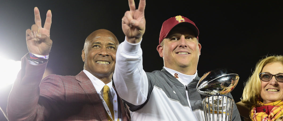 PASADENA, CA - JANUARY 02: USC Trojans athletic director Lynn Swann (L) and USC Trojans head coach Clay Helton (R) pose with the 2017 Rose Bowl trophy after defeating the Penn State Nittany Lions 52-49 to win the 2017 Rose Bowl Game presented by Northwestern Mutual at the Rose Bowl on January 2, 2017 in Pasadena, California. (Photo by Harry How/Getty Images)