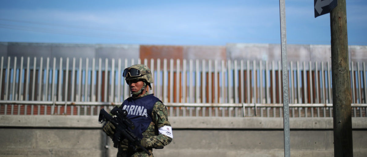 A Mexican soldier stands guard in front of the border wall with the United States, outside of a sports centre used as a temporary shelter used for migrants in Tijuana, Mexico, November 21, 2018. REUTERS/Hannah McKay