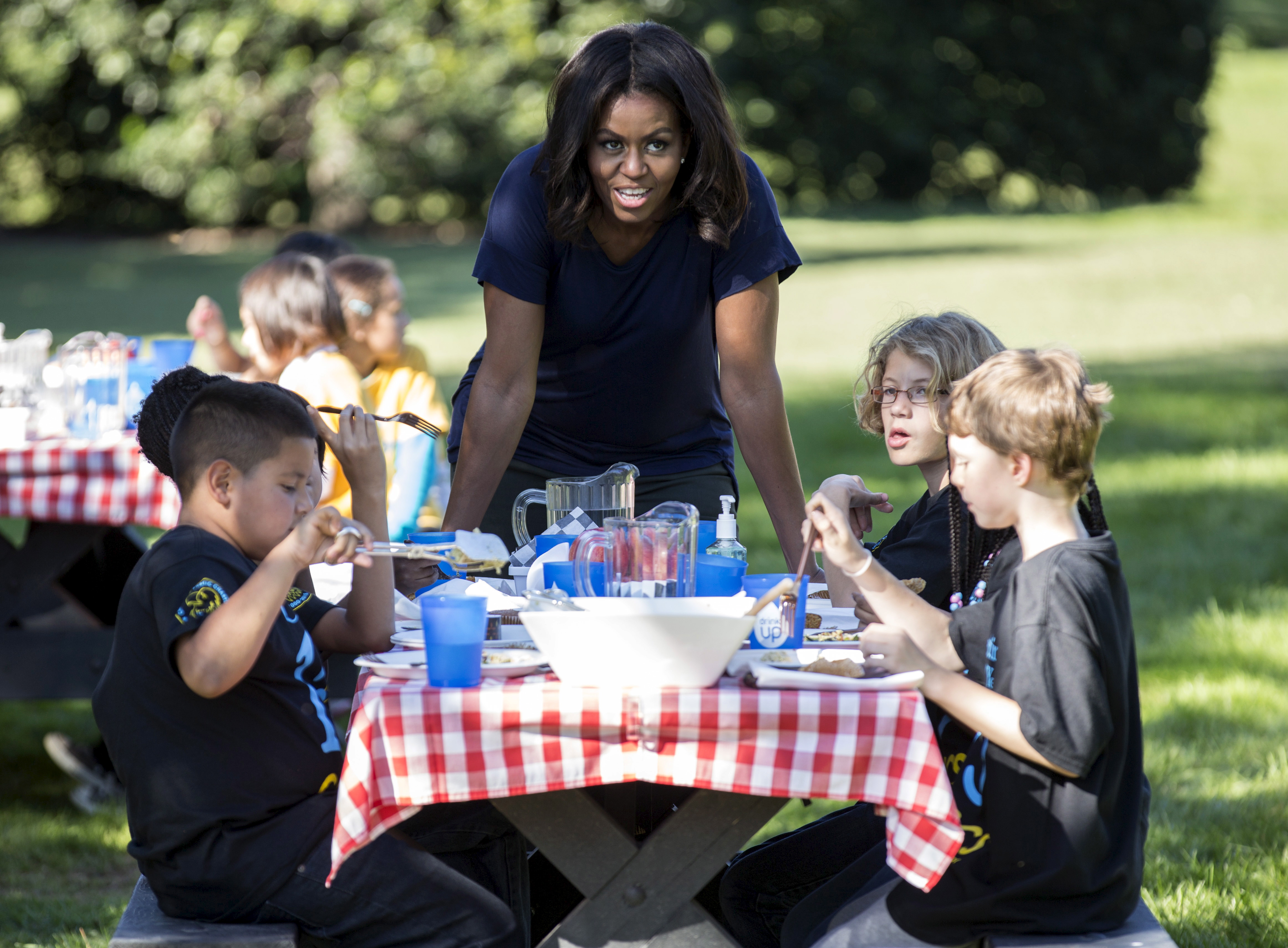 U.S. first lady Michelle Obama talks to local elementary school students after picking vegetables with them during the annual fall harvest of the White House Kitchen Garden at the White House in Washington, October 6, 2015. REUTERS/Joshua Roberts
