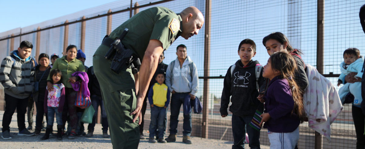 A group of Central American migrants is questioned about their children's health after surrendering to U.S. Border Patrol Agents south of the U.S.-Mexico border fence in El Paso