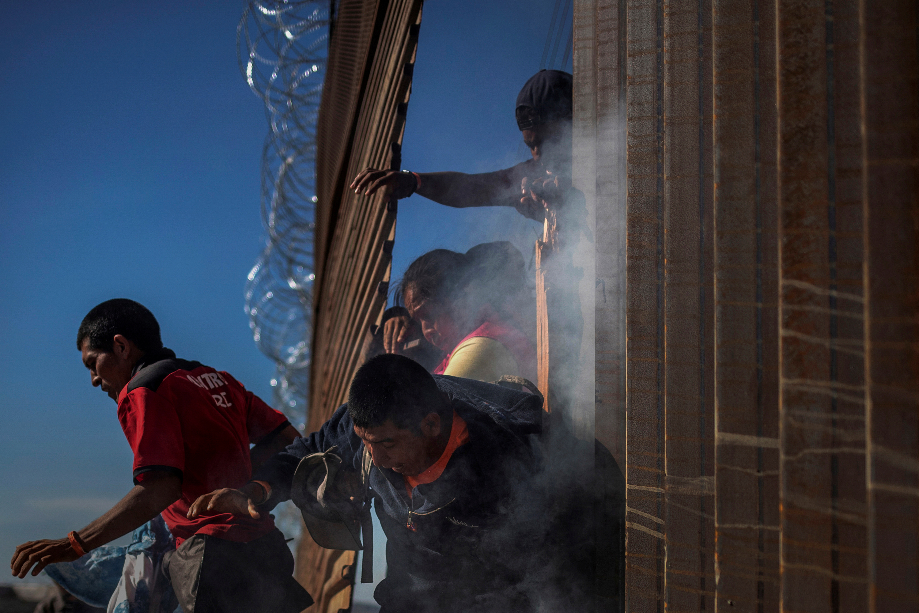 Migrants, part of a caravan of thousands from Central America trying to reach the United States, return to Mexico after being hit by tear gas by U.S. Customs and Border Protection officials after attempting to illegally cross the border wall into the United States in Tijuana, Mexico November 25, 2018. REUTERS/Adrees Latif.