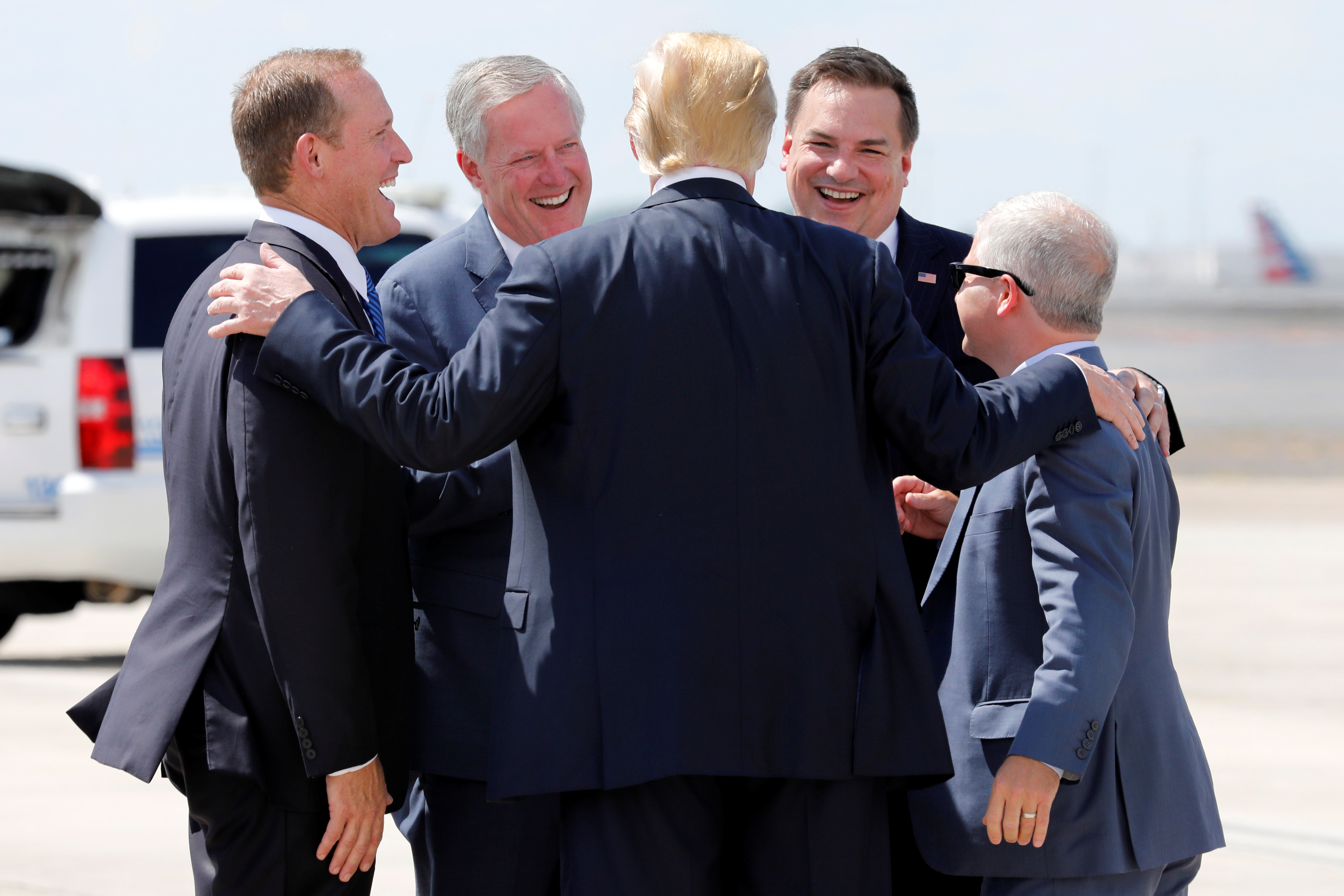 U.S. President Donald Trump greets Republican Representatives from North Carolina Ted Budd (L), Mark Meadows (2nd L) and Richard Hudson (2nd R) upon his arrival at Charlotte Douglas International Airport in Charlotte, NC, U.S., August 31, 2018. REUTERS/Yuri Gripas - RC1EBA34B780