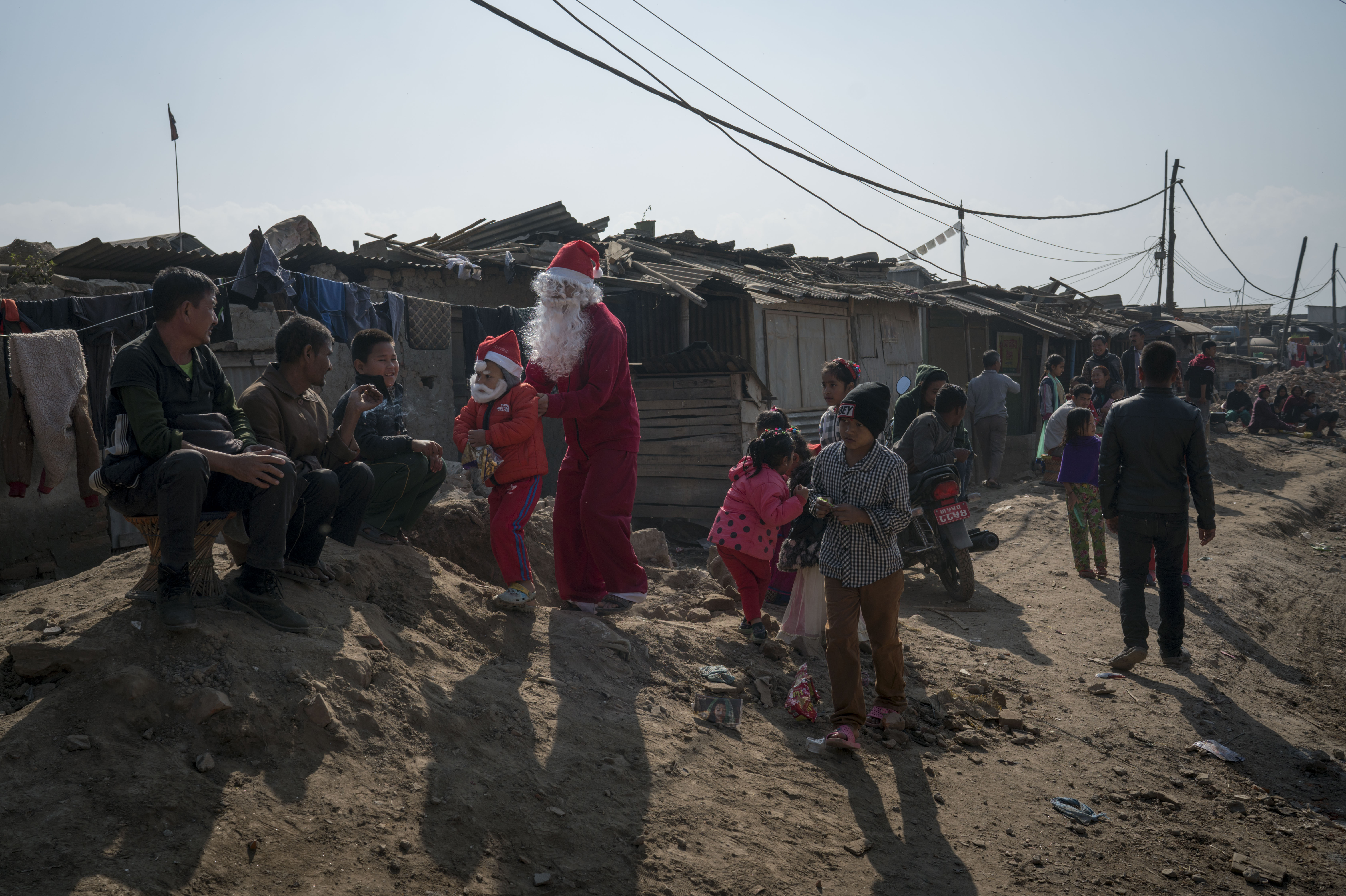 KATHMANDU, KATHMANDU - DECEMBER 25: Christians wearing Santa costumes celebrate Christmas in a slum area by handing out sweets on December 25, 2016 in Kathmandu, Nepal. Many Christians in Nepal celebrate Christmas by copying traditional European Christmas symbols. (Photo by Tom Van Cakenberghe/Getty Images)