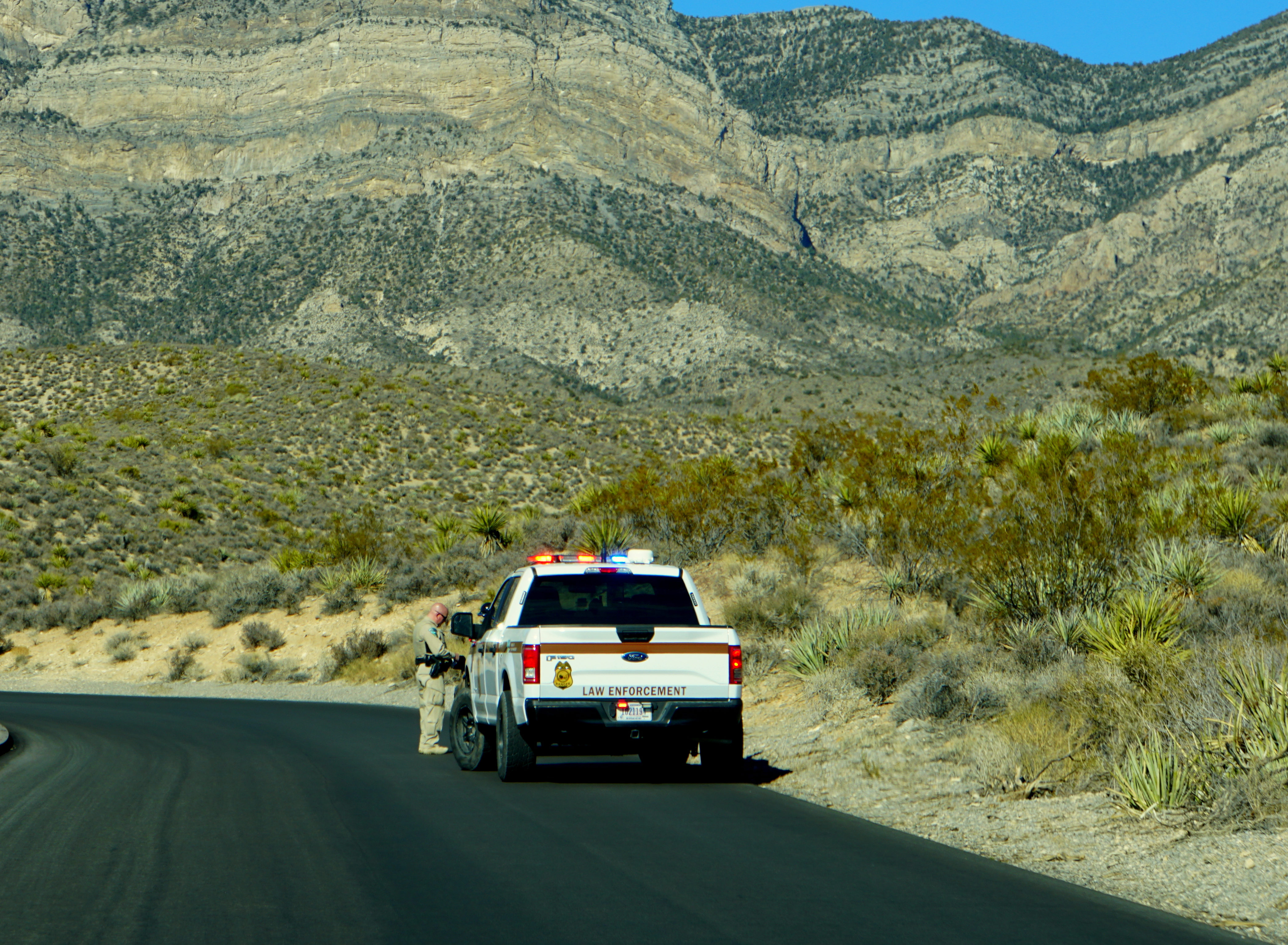 Las Vegas, Nevada, U.S.A - December 31, 2018 - Law enforcement officer patrolling the road near Red Rock Canyon National Conservation Area. Source: Shutterstock