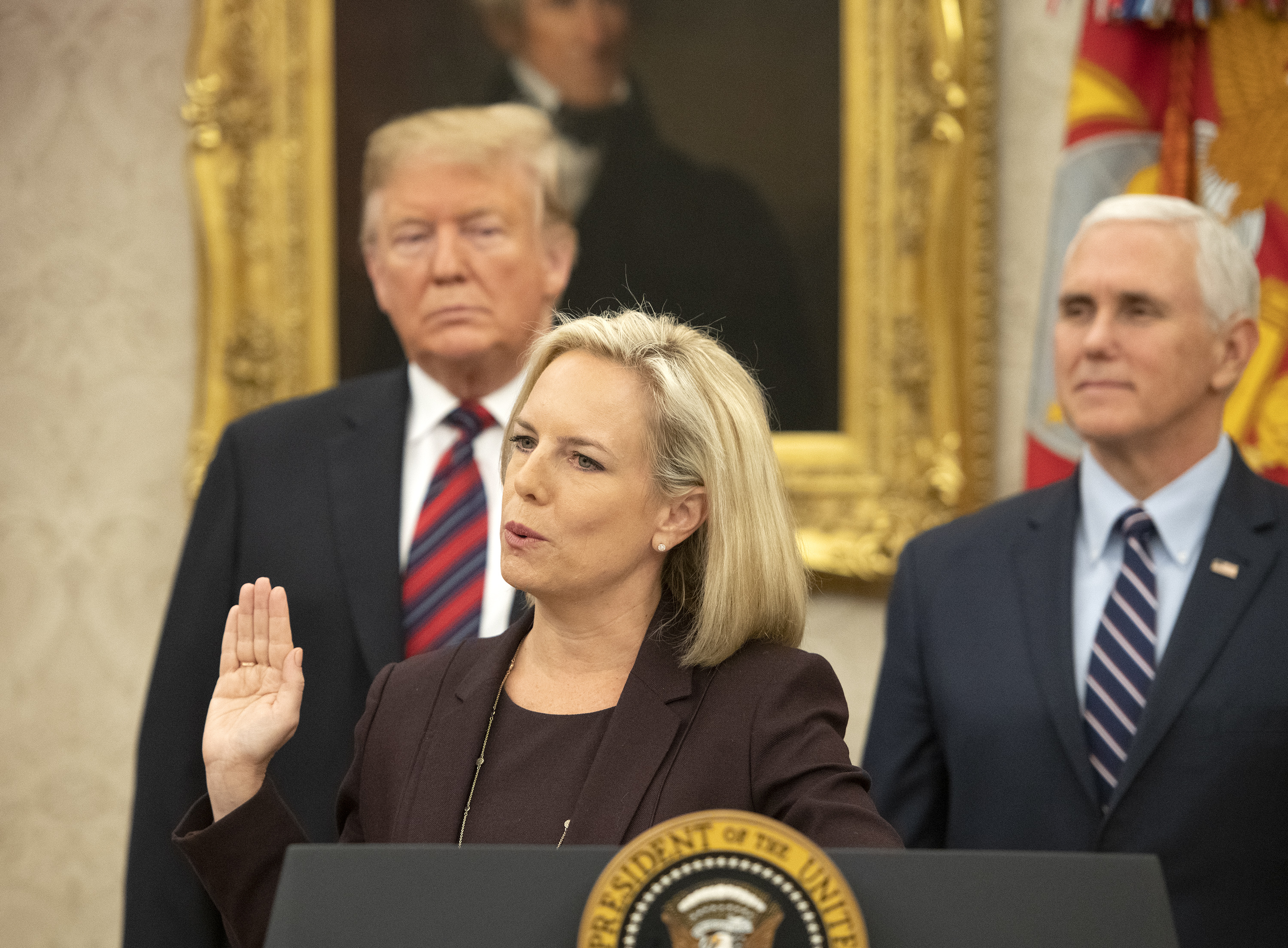 WASHINGTON, DC - JANUARY 19: United States Secretary of Homeland Security (DHS) Kirstjen Nielsen, center, administers the oath of citizenship to five people as U.S. President Donald Trump, left, and Vice President Mike Pence, right look on during a naturalization ceremony in the Oval Office of the White House in Washington, DC on Saturday, January 19, 2019. (Photo by Ron Sachs-Pool/Getty Images)