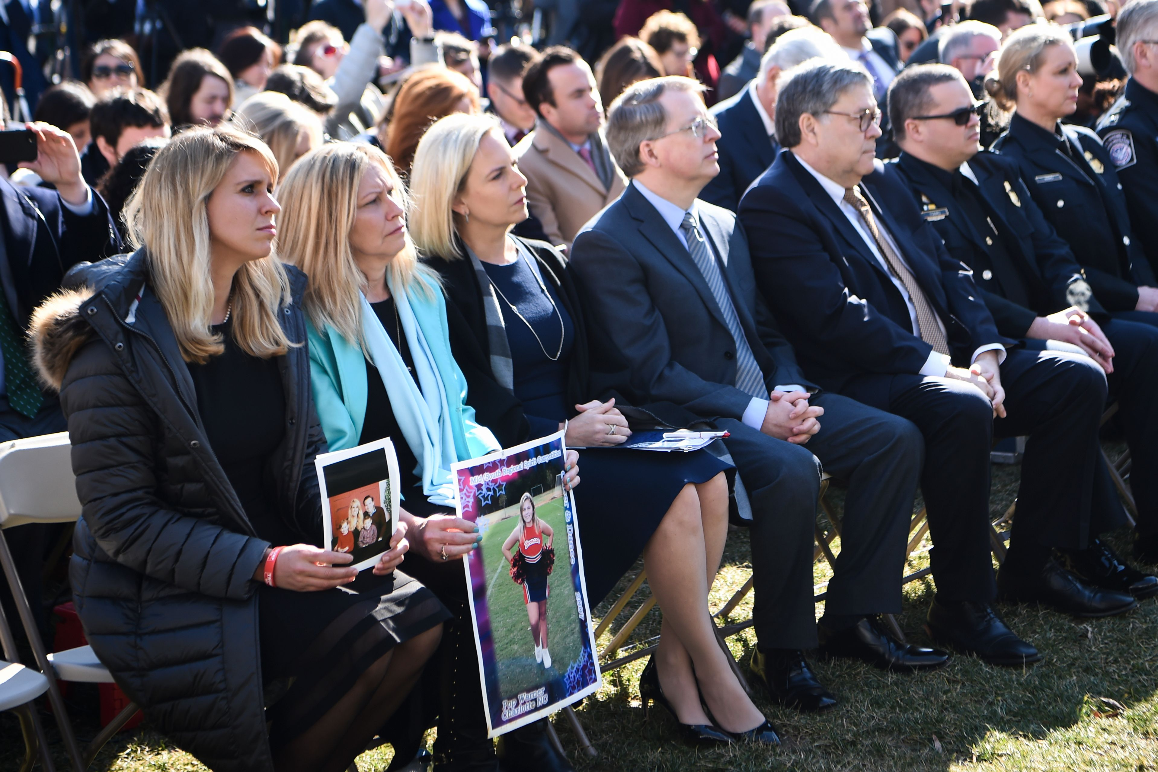 Family members hold portraits of loved one that were victims of crimes committed by undocumented immigrants, before US President Donald Trump delivers remarks, as US Secretary of Homeland Security Kirstjen Nielsen (3L), and US Attorney General William Barr (3R) look on in the Rose Garden at the White House in Washington, DC on February 15, 2019. (Photo: BRENDAN SMIALOWSKI/AFP/Getty Images)