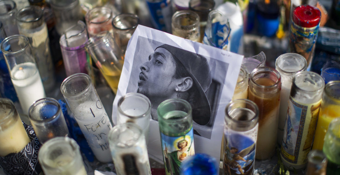 A photo of rapper Nipsey Hussle, 33, is seen among candles as people gather to mourn him on April 1, 2019 in Los Angeles, California. The Grammy-nominated artist was gunned down in broad daylight two days ago in front of The Marathon Clothing store he founded in 2017 on the day he was scheduled to meet with Los Angeles Police Department brass to discuss ways of stopping gang violence. (Photo by David McNew/Getty Images)