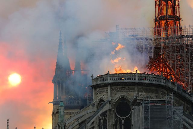 Smoke billows as flames destroy the roof of the landmark Notre-Dame Cathedral in central Paris on April 15, 2019. - A major fire broke out at the landmark Notre-Dame Cathedral in central Paris sending flames and huge clouds of grey smoke billowing into the sky, the fire service said. The flames and smoke plumed from the spire and roof of the gothic cathedral, visited by millions of people a year, where renovations are currently underway. (Photo credit: FRANCOIS GUILLOT/AFP/Getty Images)