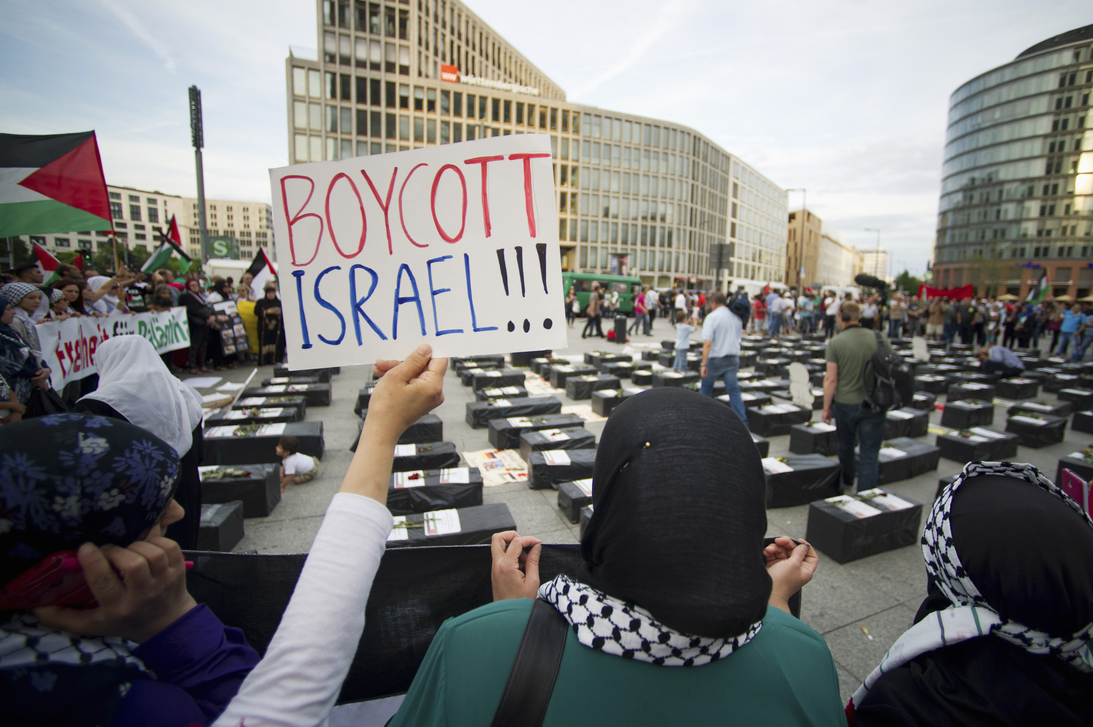 "A woman holds a sign which reads ""Boycott Israel"" in front of symbolic coffins while attending a demonstration supporting Palestine, in Berlin August 1, 2014. REUTERS/Steffi Loos"