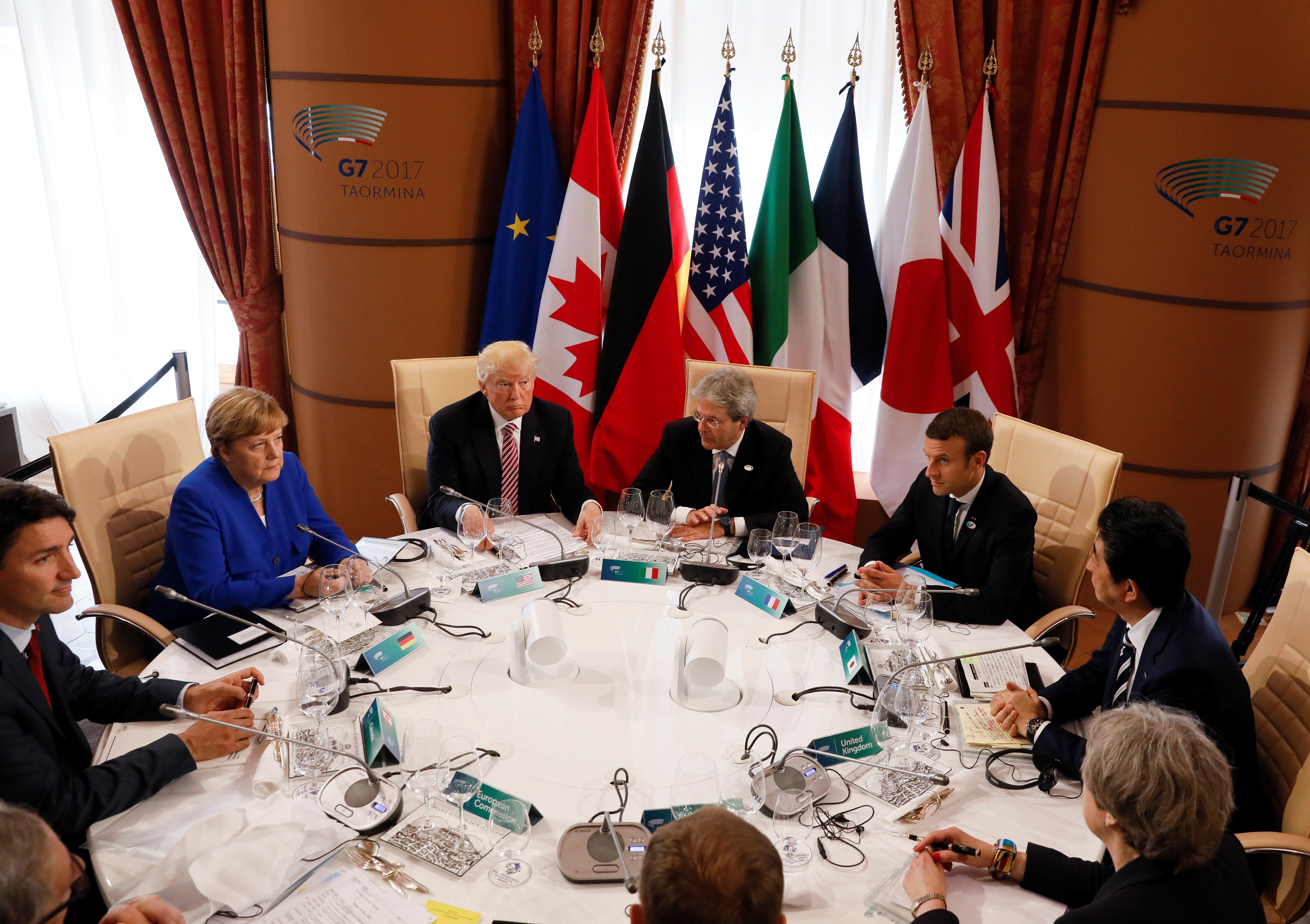 (L-R) Canadian Prime Minister Justin Trudeau, German Chancellor Angela Merkel, U.S. President Donald Trump, Italian Prime Minister Paolo Gentiloni, French President Emmanuel Macron, Japanese Prime Minister Shinzo Abe, Britain's Prime Minister Theresa May, European Council President Donald Tusk and European Commission President Jean-Claude Juncker sit around a table during the G7 Summit in Taormina, Sicily, Italy, May 26, 2017. REUTERS/Jonathan Ernst