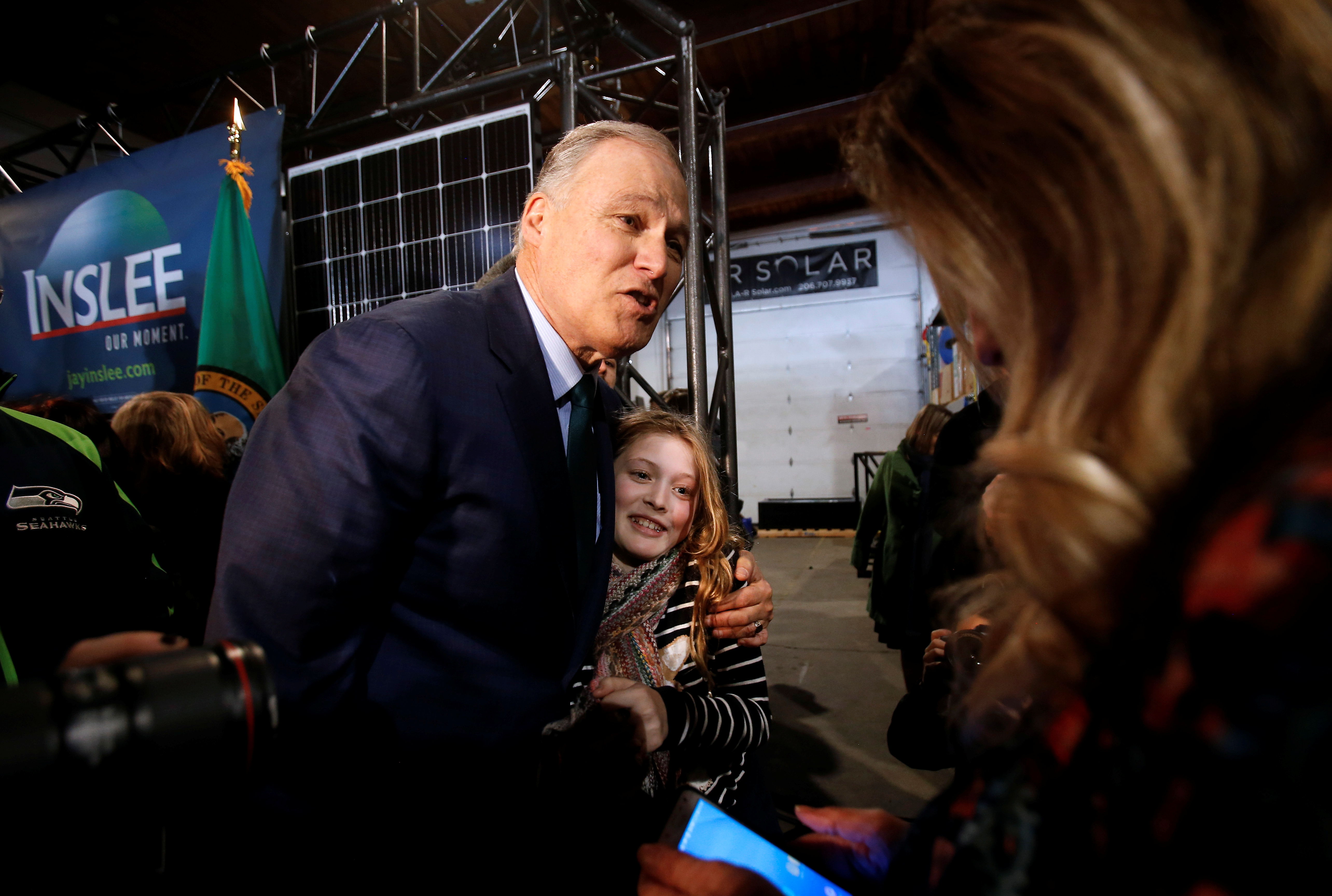 Washington state Governor Jay Inslee hugs Noreus, 11, of Redmond, Washington during a news conference to announce his decision to seek the Democratic Party's nomination for president in 2020 at A&R Solar in Seattle