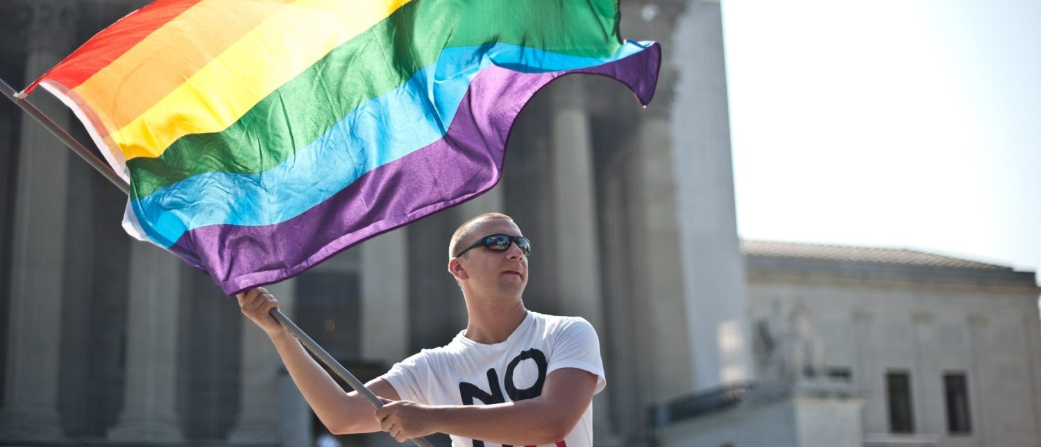 A gay rights activist waves a rainbow flag in front of the Supreme Court on June 25, 2013. (Nicholas Kamm/AFP/Getty Images)
