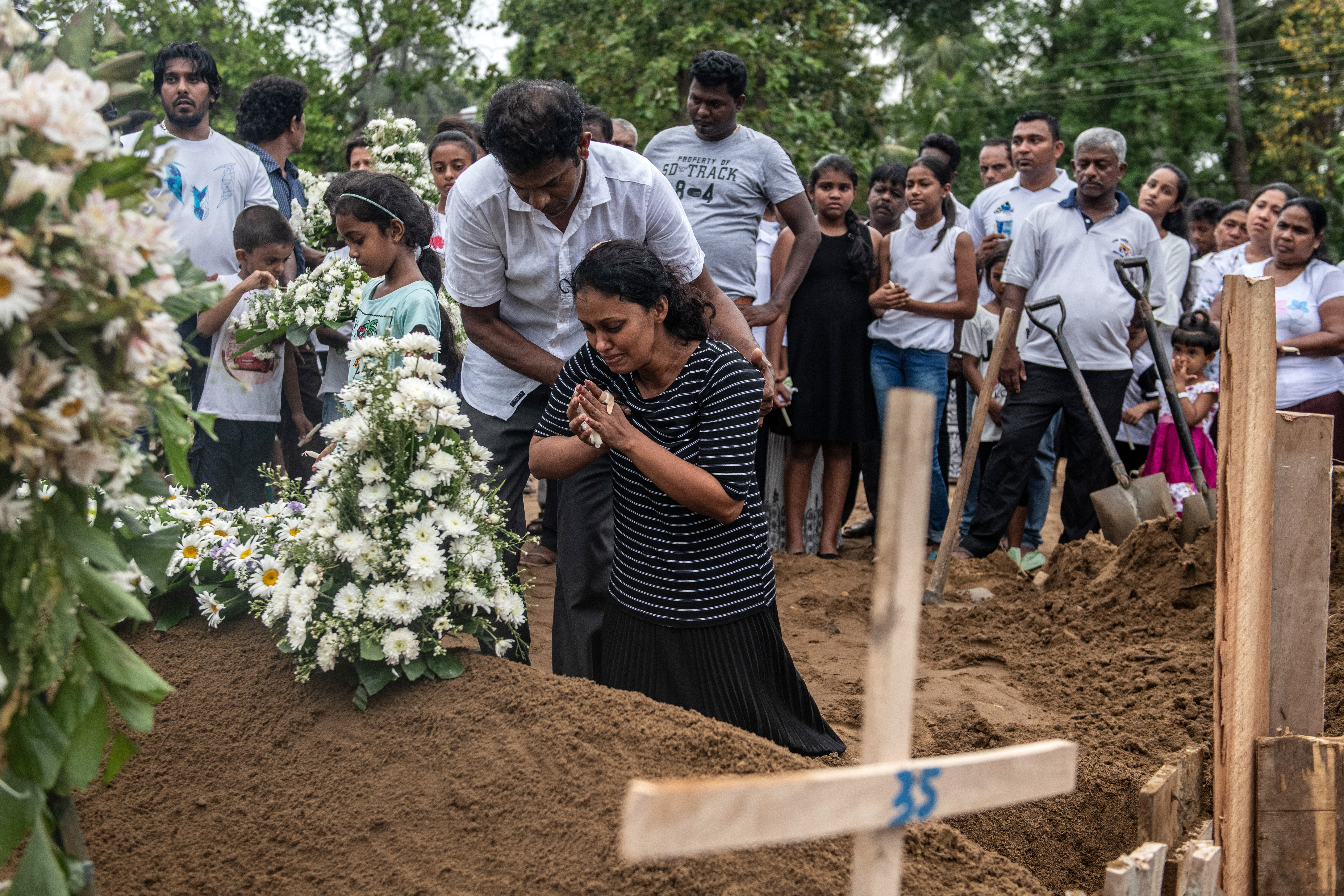 NEGOMBO, SRI LANKA - APRIL 25: A woman grieves at the grave after a funeral for a person killed in the Easter Sunday attack on St Sebastian's Church, on April 25, 2019 in Negombo, Sri Lanka. (Photo by Carl Court/Getty Images)