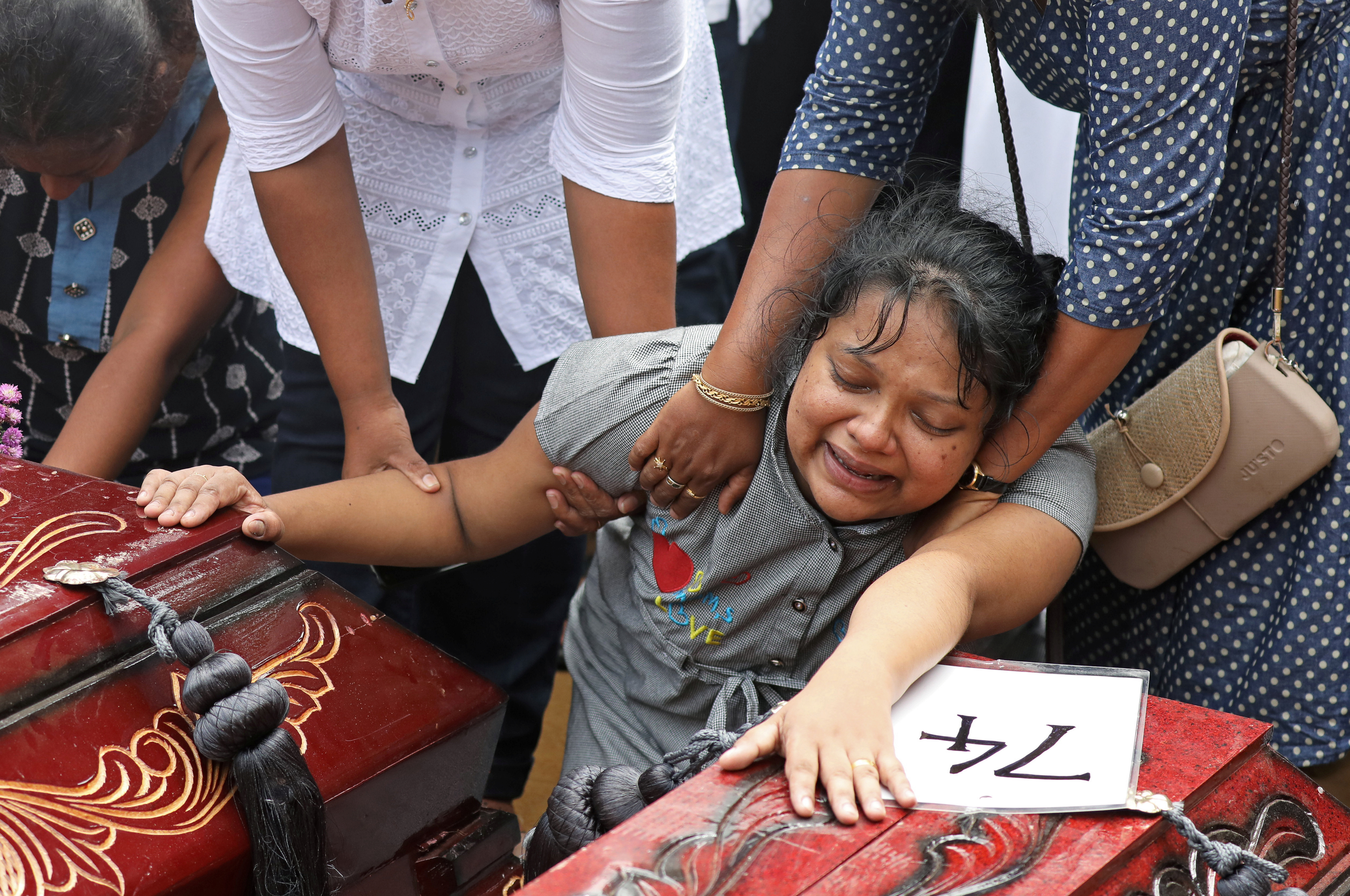 A woman reacts next to two coffins during a mass burial of victims, two days after a string of suicide bomb attacks on churches and luxury hotels across the island on Easter Sunday, at a cemetery near St. Sebastian Church in Negombo, Sri Lanka April 23, 2019. REUTERS/Athit Perawongmetha