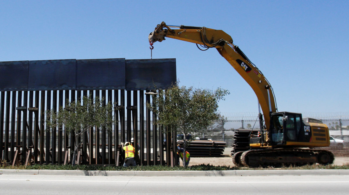 Construction workers are seen next to heavy machinery while replacing a section of the old Mexico-U.S. border as seen from Tijuana, Mexico, June 28, 2018. REUTERS/Jorge Dunes