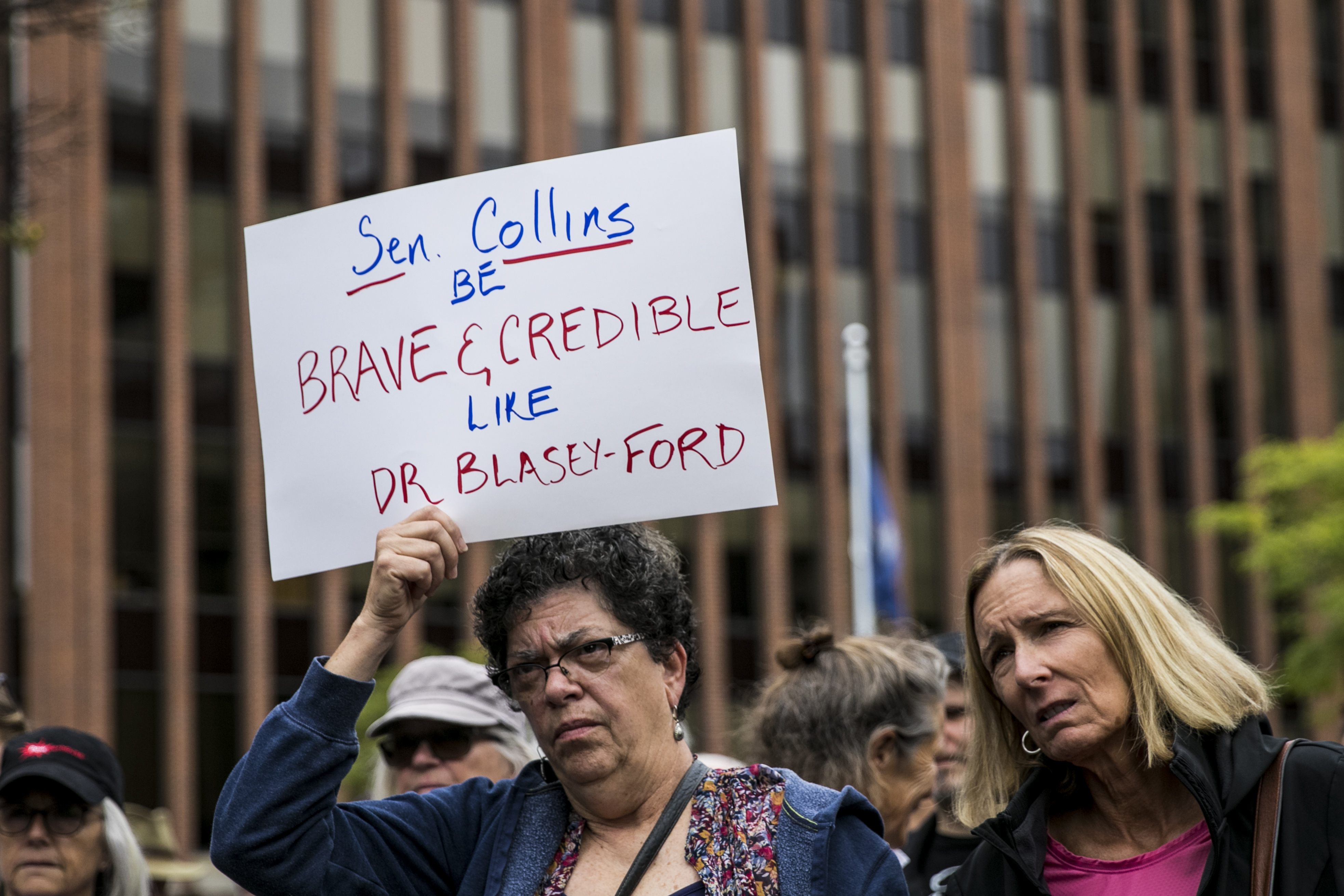 Yvonne Berry, left, of Portland, and Wendy Keeler, of Cape Elizabeth, gather with protestors across the street from Sen. Susan Collins' office to urge Sen. Collins to vote no on the confirmation of Supreme Court nominee Brett Kavanaugh (Sarah Rice/Getty Images)