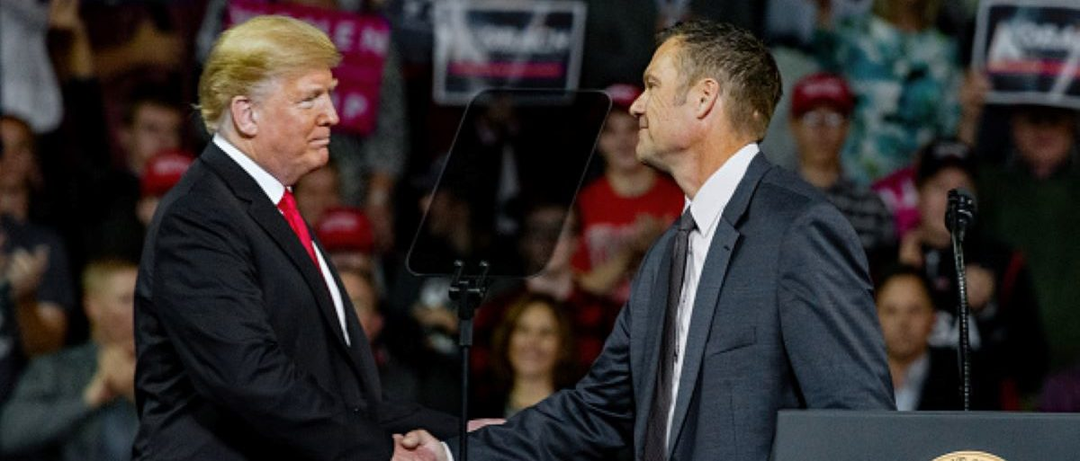 Preisdent Donald Trump, left, shakes hands with Kansas Secretary of State and current Republican candidate for Kansas governor Kris Kobach during President Trump's MAGA rally held in Landon Arena in Topeka, Kansas, October 6, 2018. (Photo by Mark Reinstein/Corbis via Getty Images)