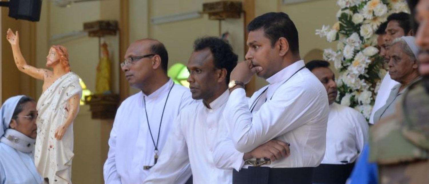 Catholic priests stand inside the church after a bomb blast in Negombo, Sri Lanka, April 21, 2019.