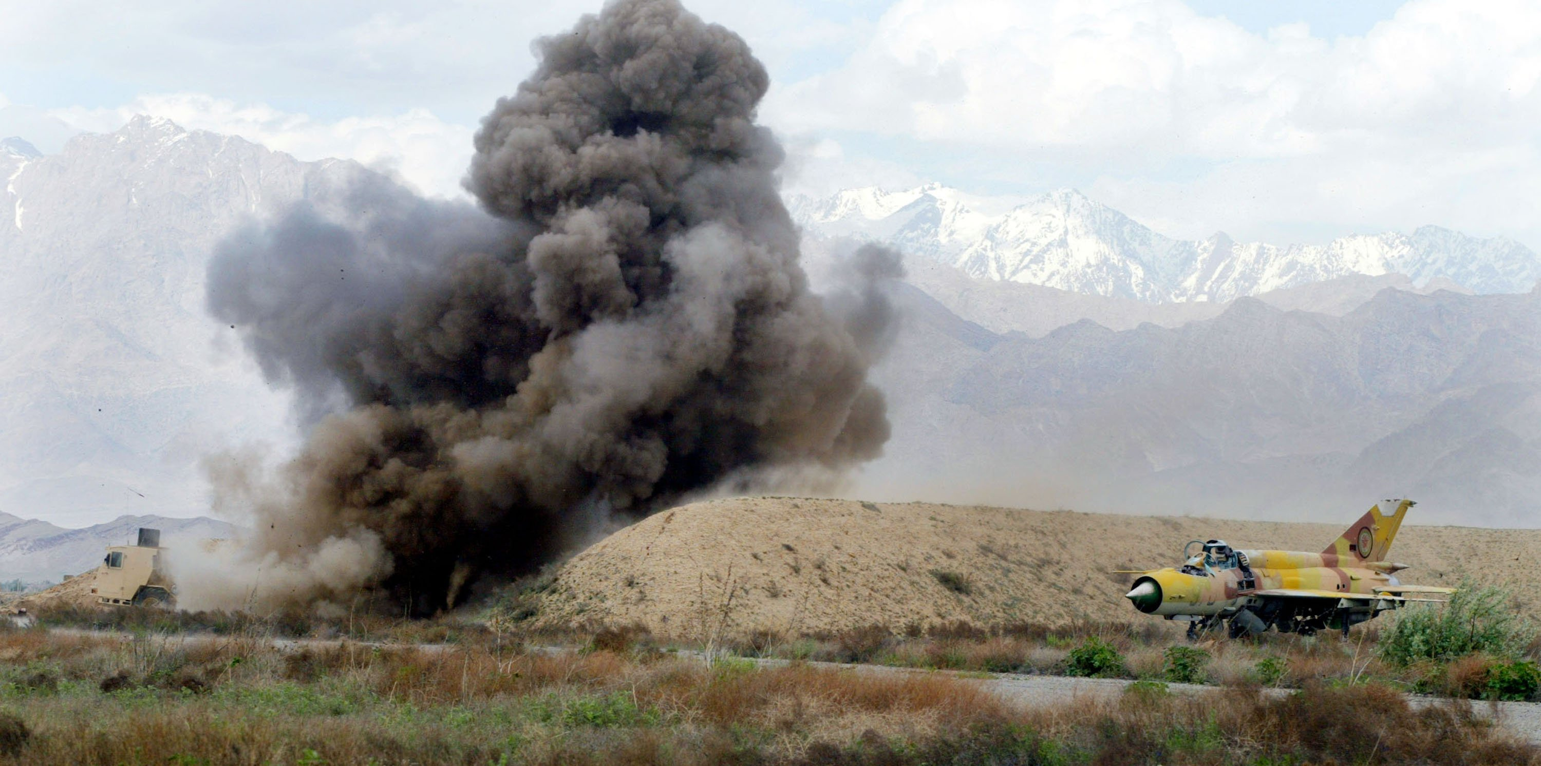 A Norwegian mine clearing machine detonates a land mine useing a flail, a series of chains that rotate and beat the ground, April 20, 2002 at the Bagram Air Base in Afghanistan. An old Russian fighter plane still sits in a bunker near the explosion. The Norwegian mine clearing team has been busy over the last months trying to clear the land around the bases in Kandahar and Bagram. (Photo by Joe Raedle/Getty Images)