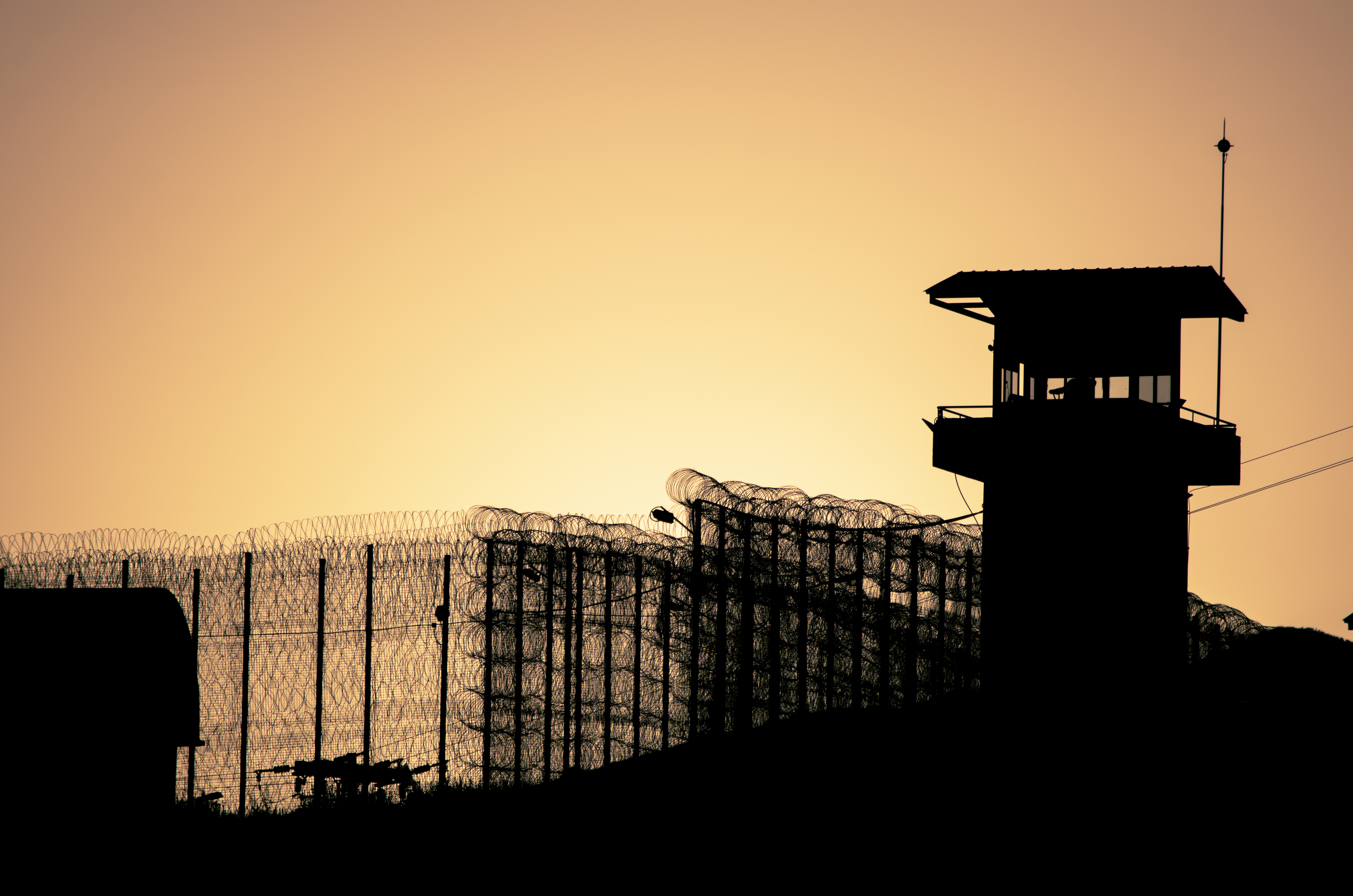 Silhouette of barbed wires and watchtower of prison in Neapolis, Crete, at sunset. (Georgios Tsichlis/Shutterstock.com)