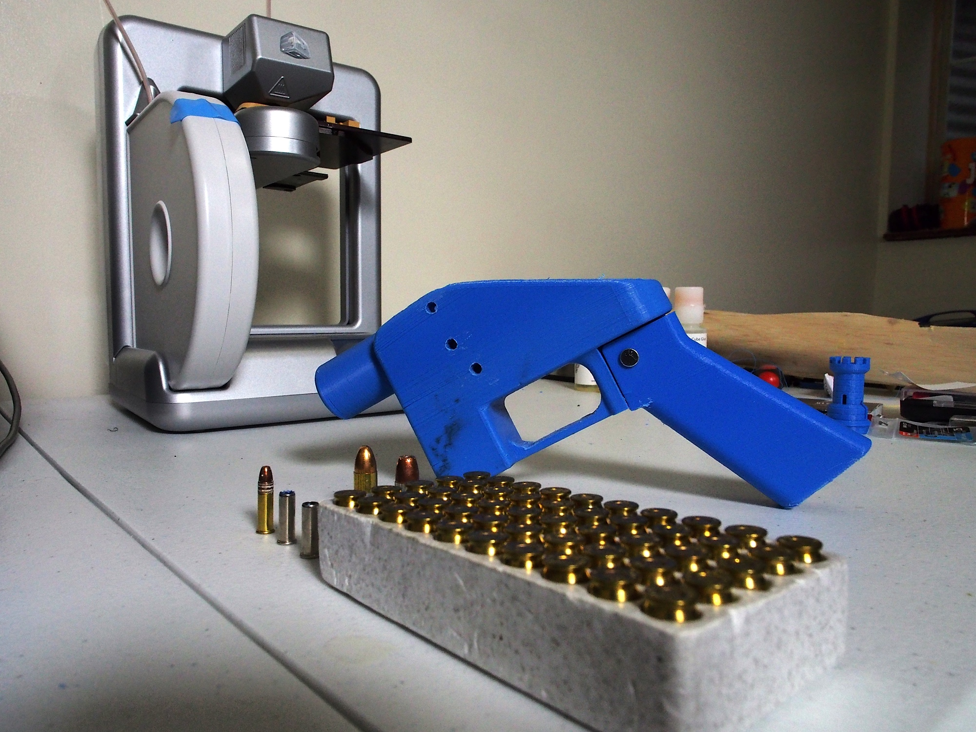 A Liberator pistol appears on July 11, 2013 next to the 3D printer on which its components were made. The single-shot handgun is the first firearm that can be made entirely with plastic components forged with a 3D printer and computer-aided design (CAD) files downloaded from the Internet. (Photo by Robert MacPherson/AFP/Getty Images)
